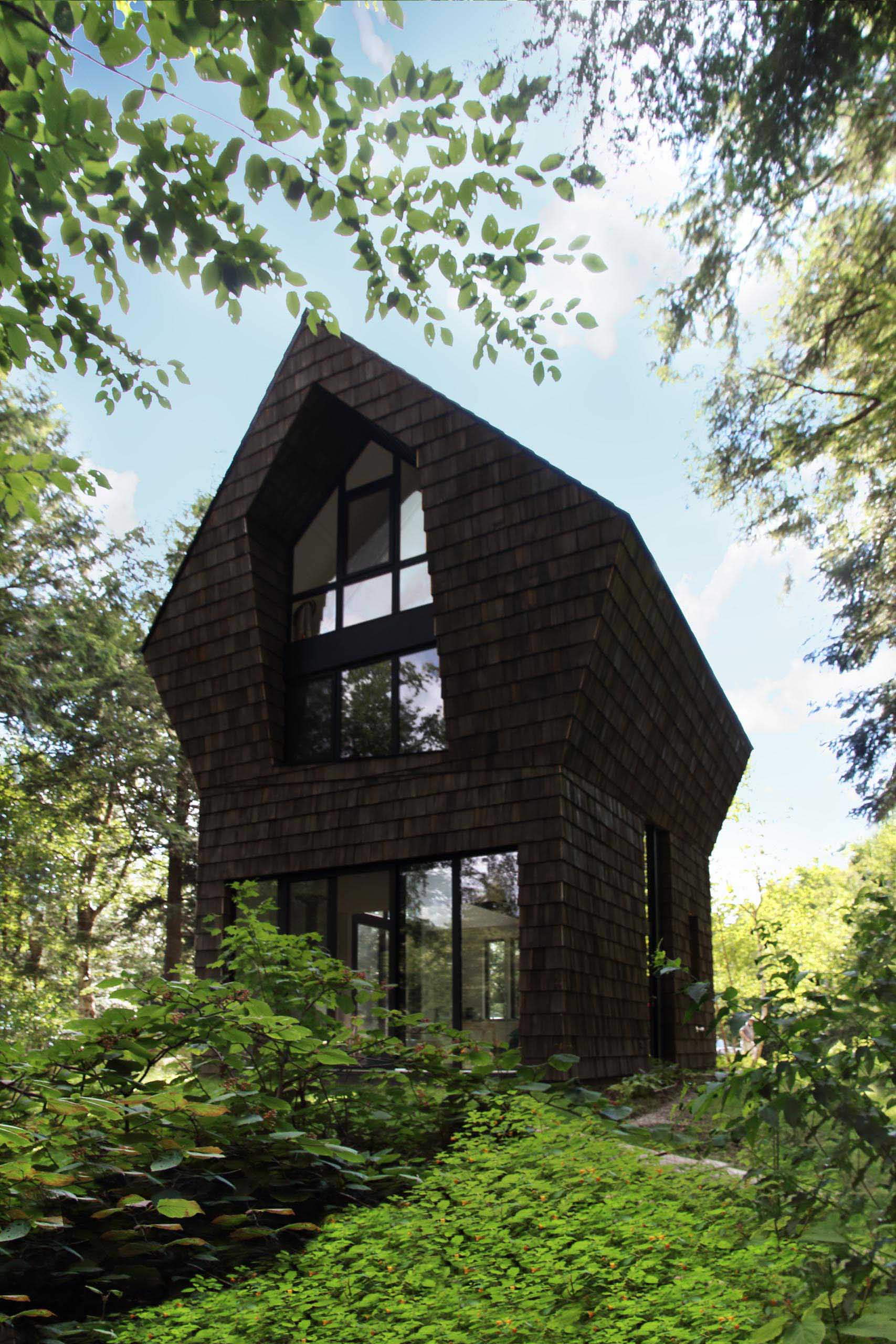 The dark cedar wood shingles of this cottage are complemented by black window and door frames throughout.