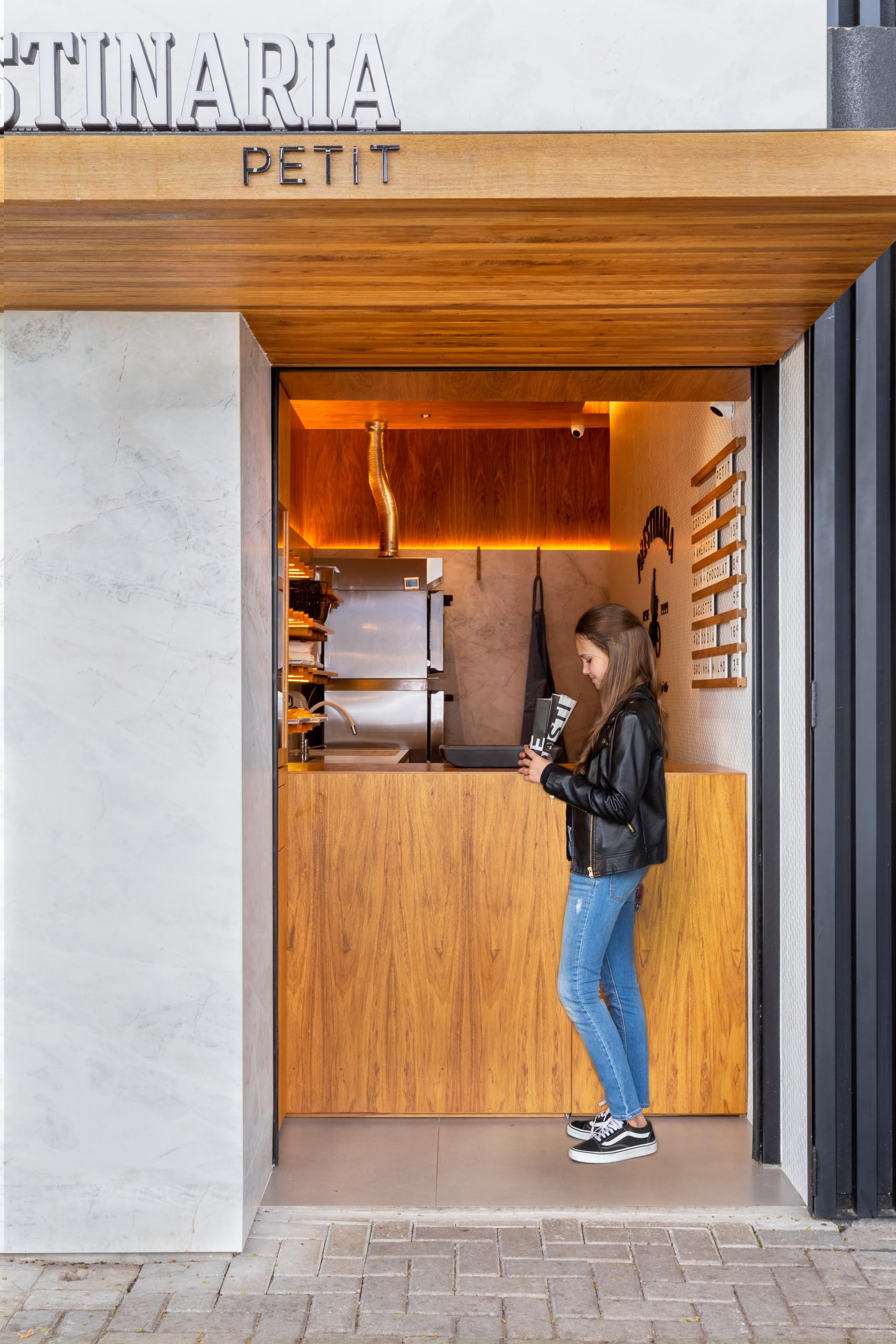 A small bakery makes use of wood dowels with hidden LED lighting to hold up shelving.