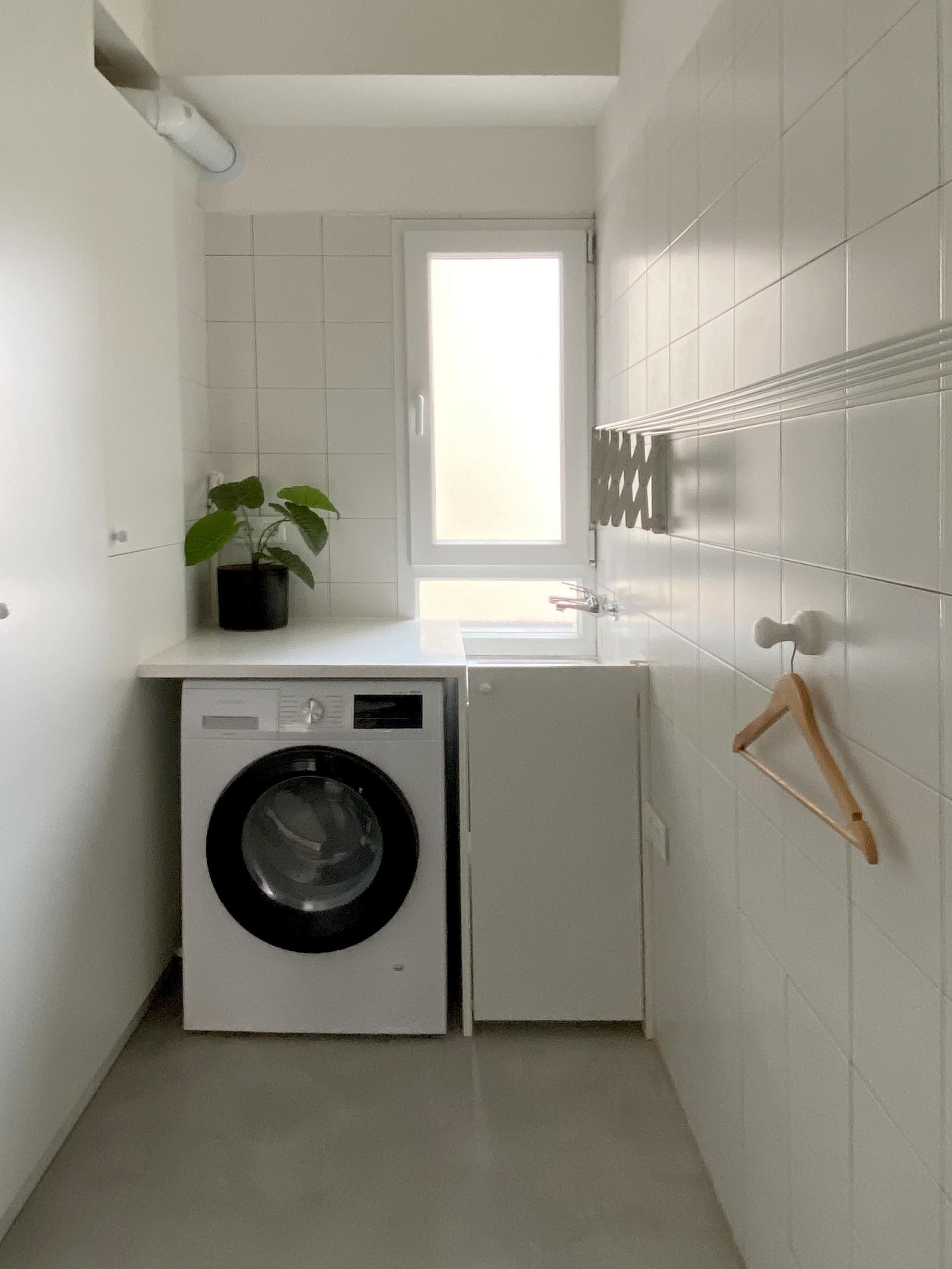 A small laundry with square white tiles and a sink below the window.
