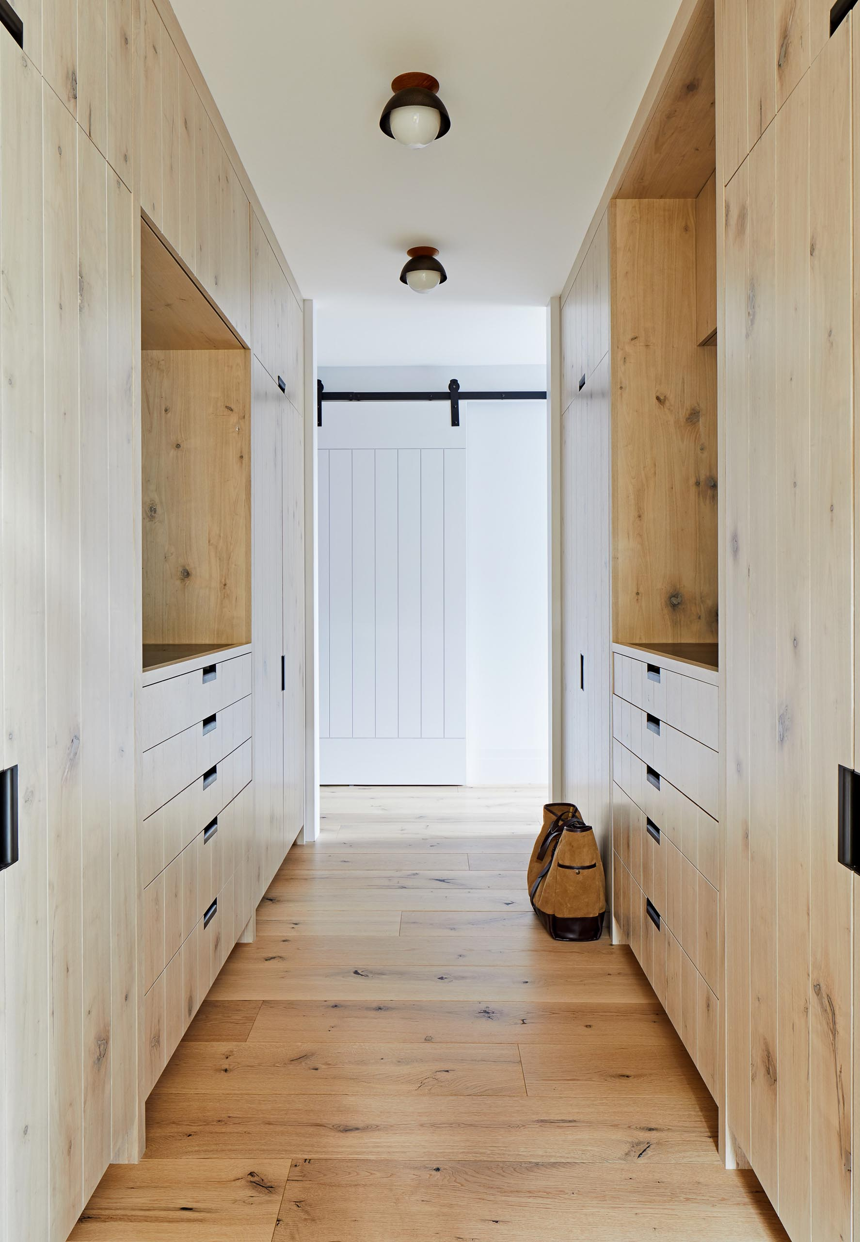 This master walk-in closet has plenty of space for storing clothes within the floor-to-ceiling wood cabinets.