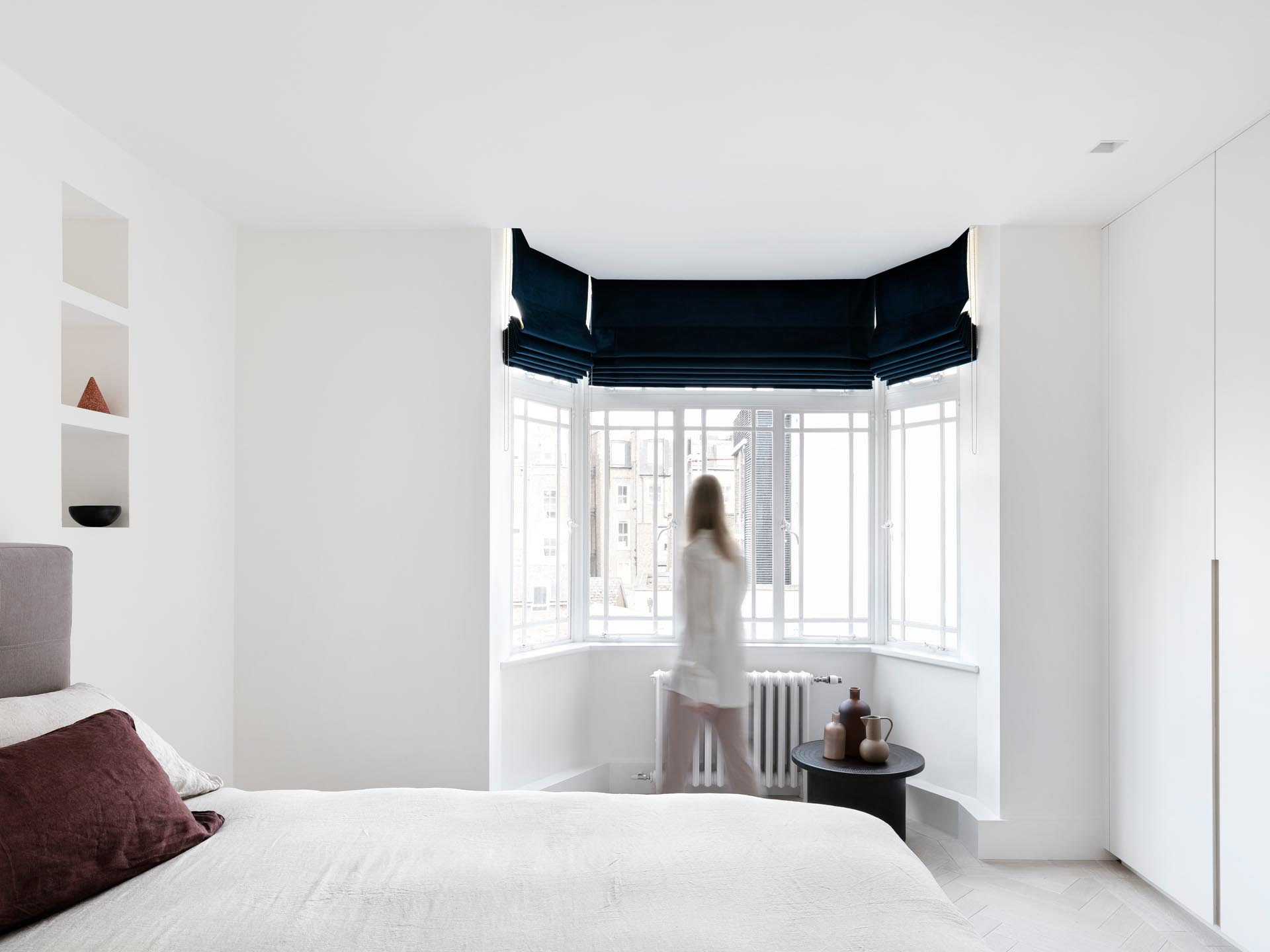 In this remodeled bedroom, the designers opened-up hidden wall niches, lowered the ceilings to hide curtain tracks, and created bespoke wardrobes.