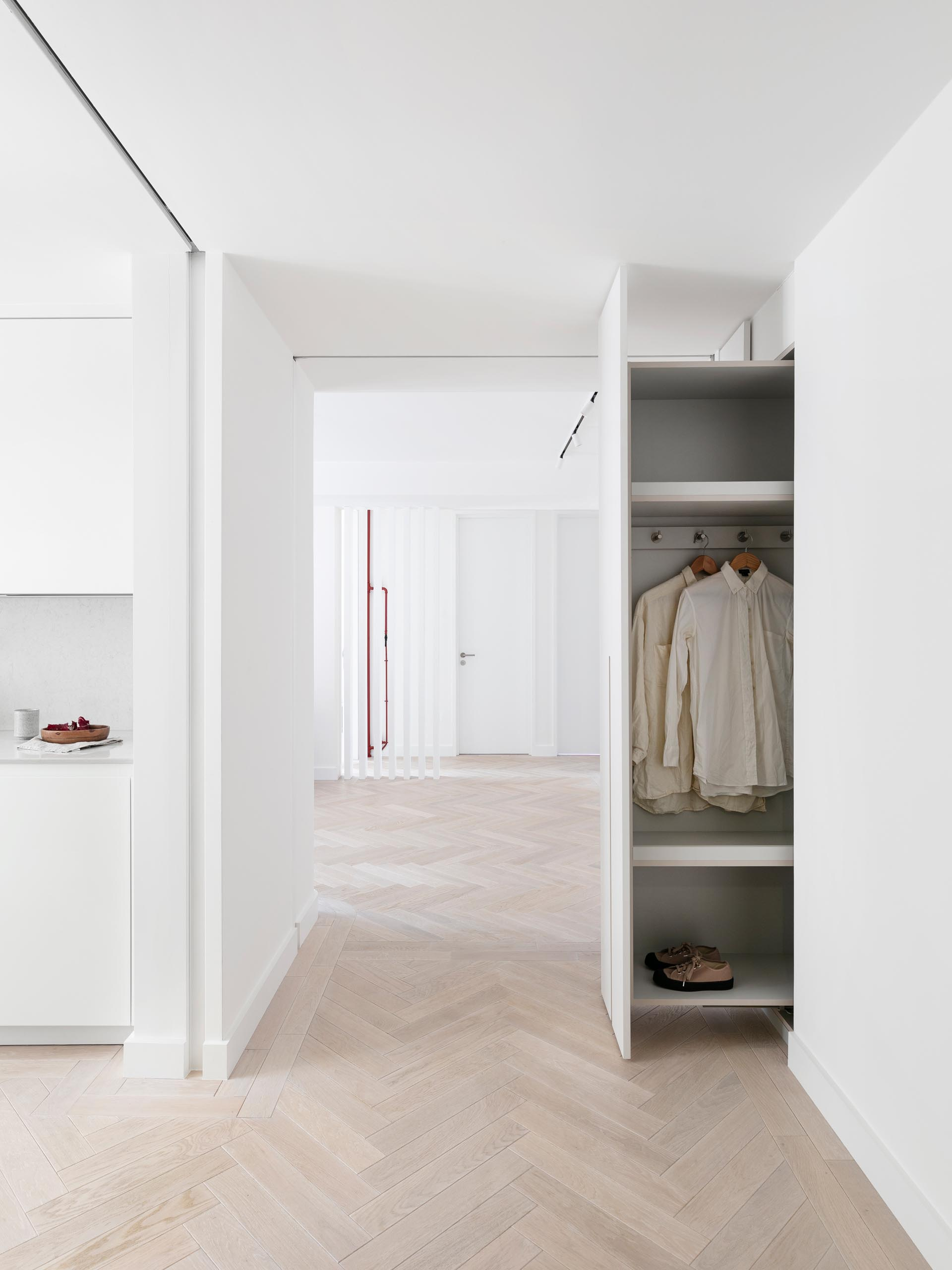 This modern entry hallway has a wall of cabinets that can be pulled out to reveal coat hangers and shoe storage.