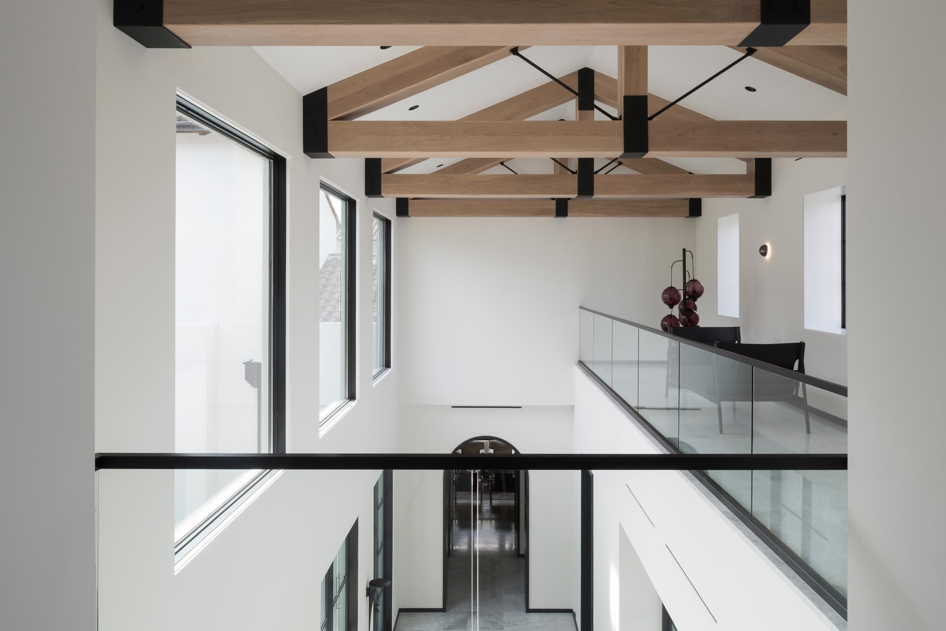 Exposed wood trusses add a natural element to the space, while the black supports match the window frames, doorways, and handrails.