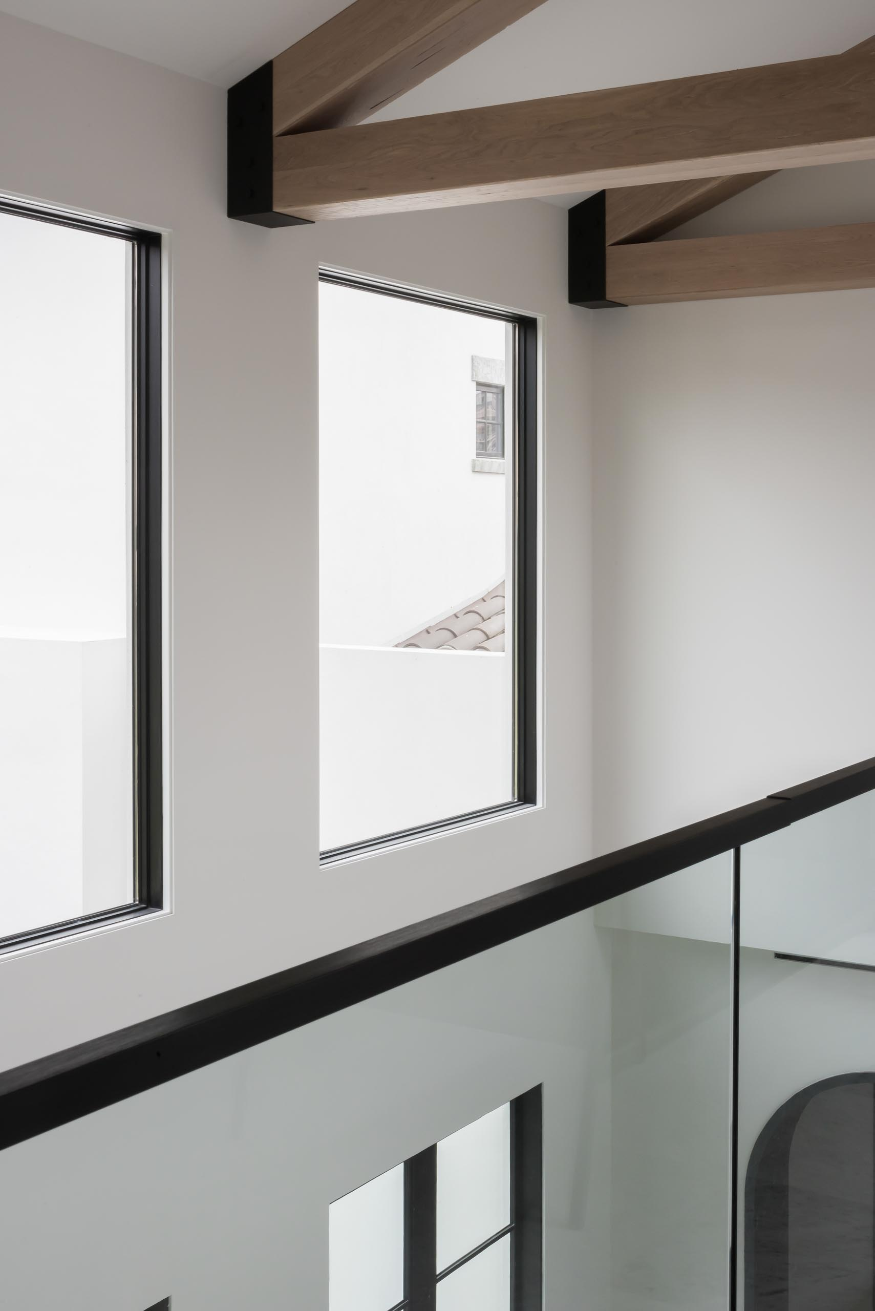 A modern interior with exposed wood trusses and black window frames.