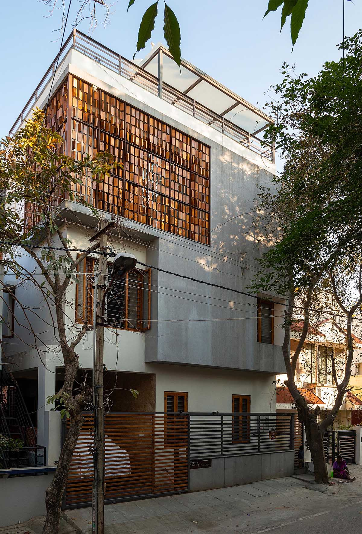 A modern house with a wood block screen that wraps around the corner of the home.