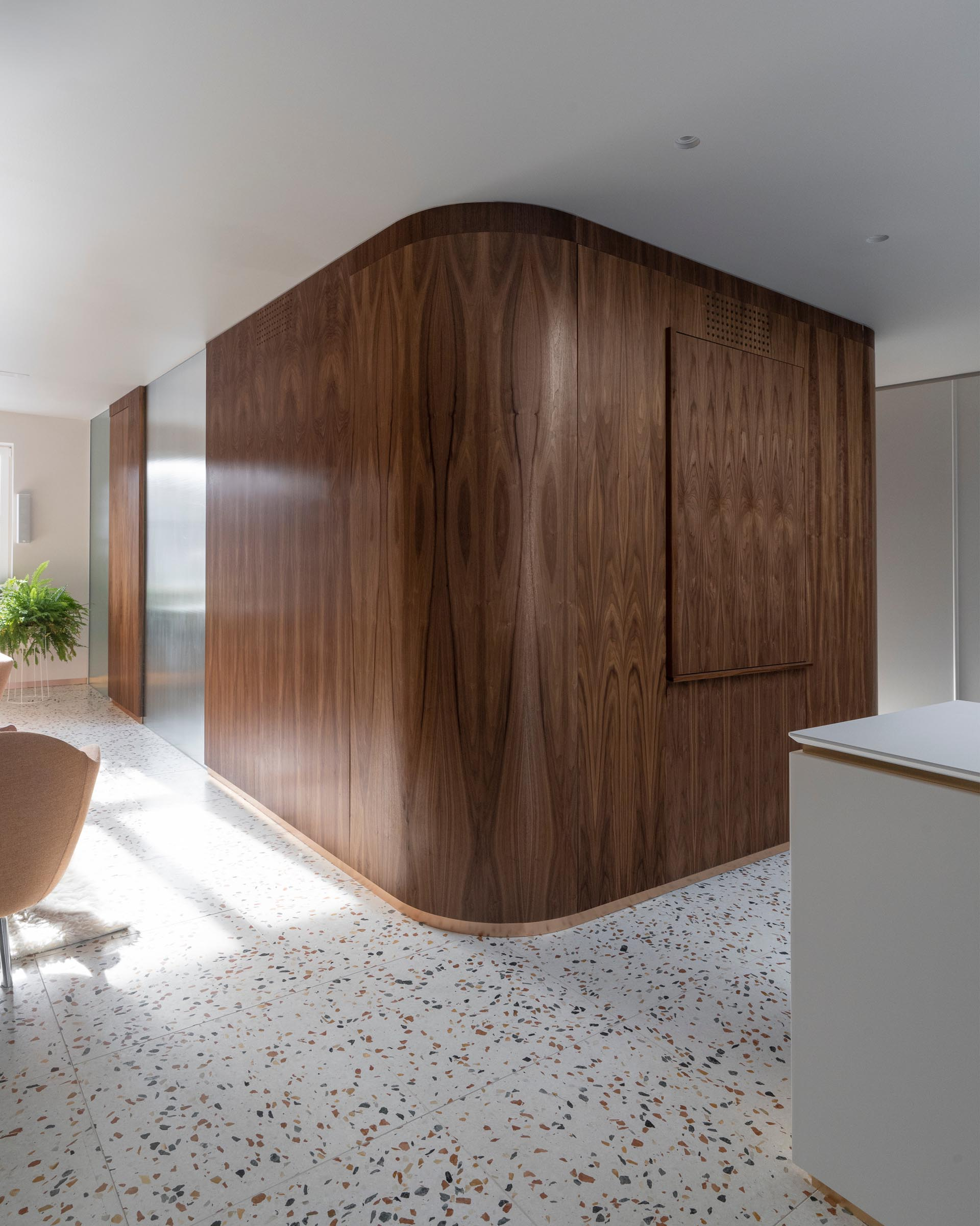 Connecting the various levels of this modern home is a central module clad in walnut that houses the staircase and a small powder room.