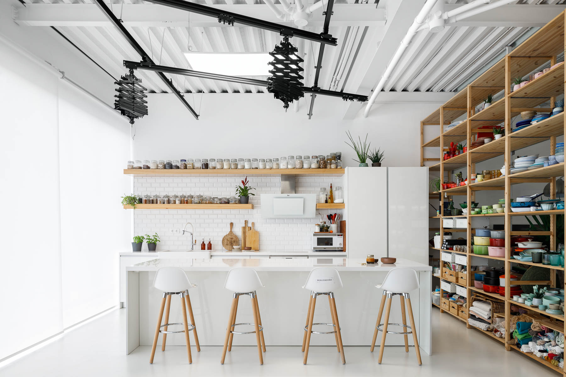 A modern office has a photo studio with a minimalist white kitchen with floating wood shelves. Adjacent to the kitchen are tall wood shelves filled with photography props and kitchen equipment.