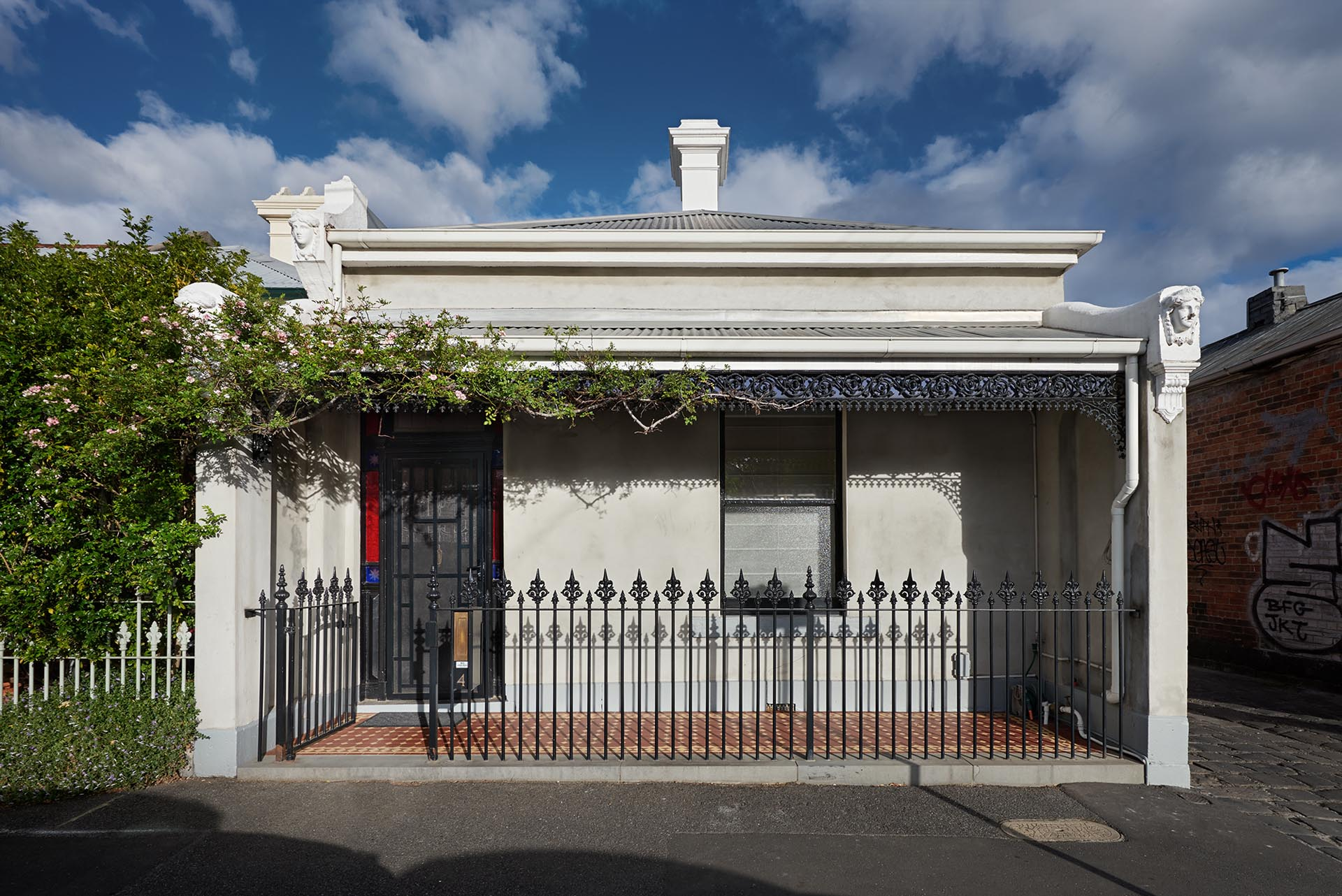 The home, located in Melbourne, Australia, has a traditional facade that includes ornate iron work and a small front porch.