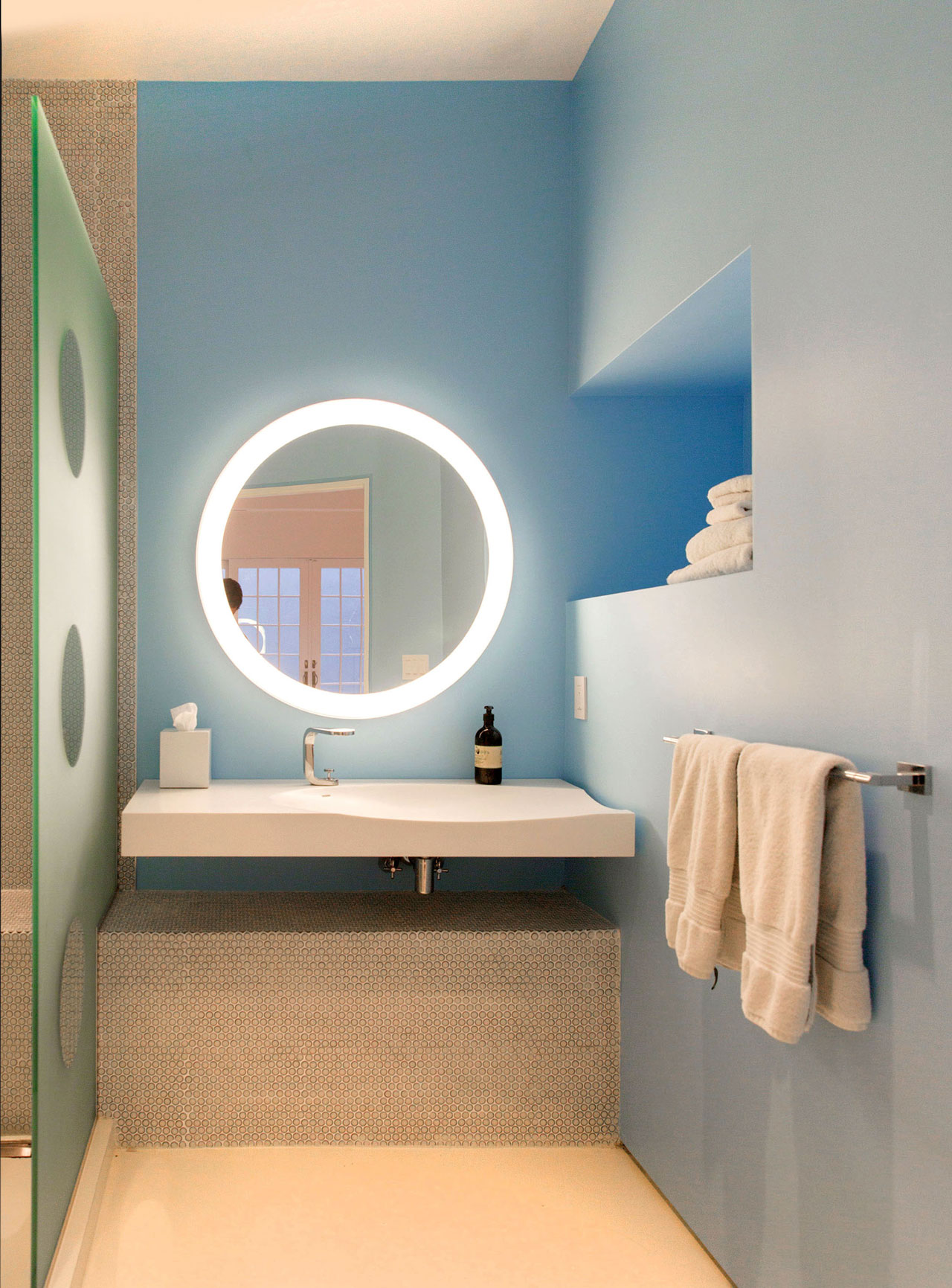 A basement bathroom that features design elements like small penny tiles, a translucent glass shower screen with clear circular windows, and a round vanity mirror with integrated lighting.