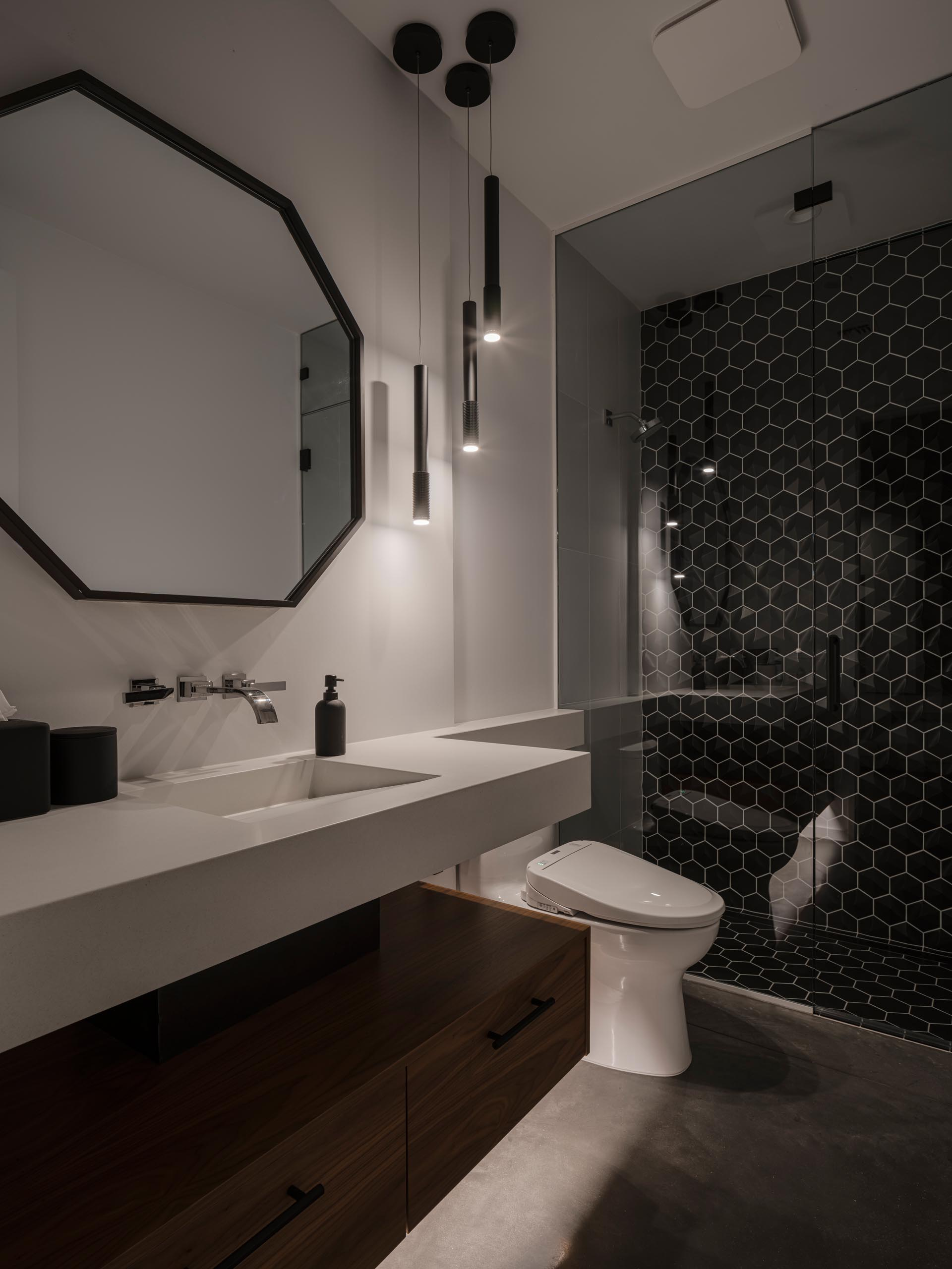 In this modern guest bathroom there's a floating vanity with wood cabinet underneath, and a large black framed octagonal mirror that complements the black hexagonal tiles in the shower.