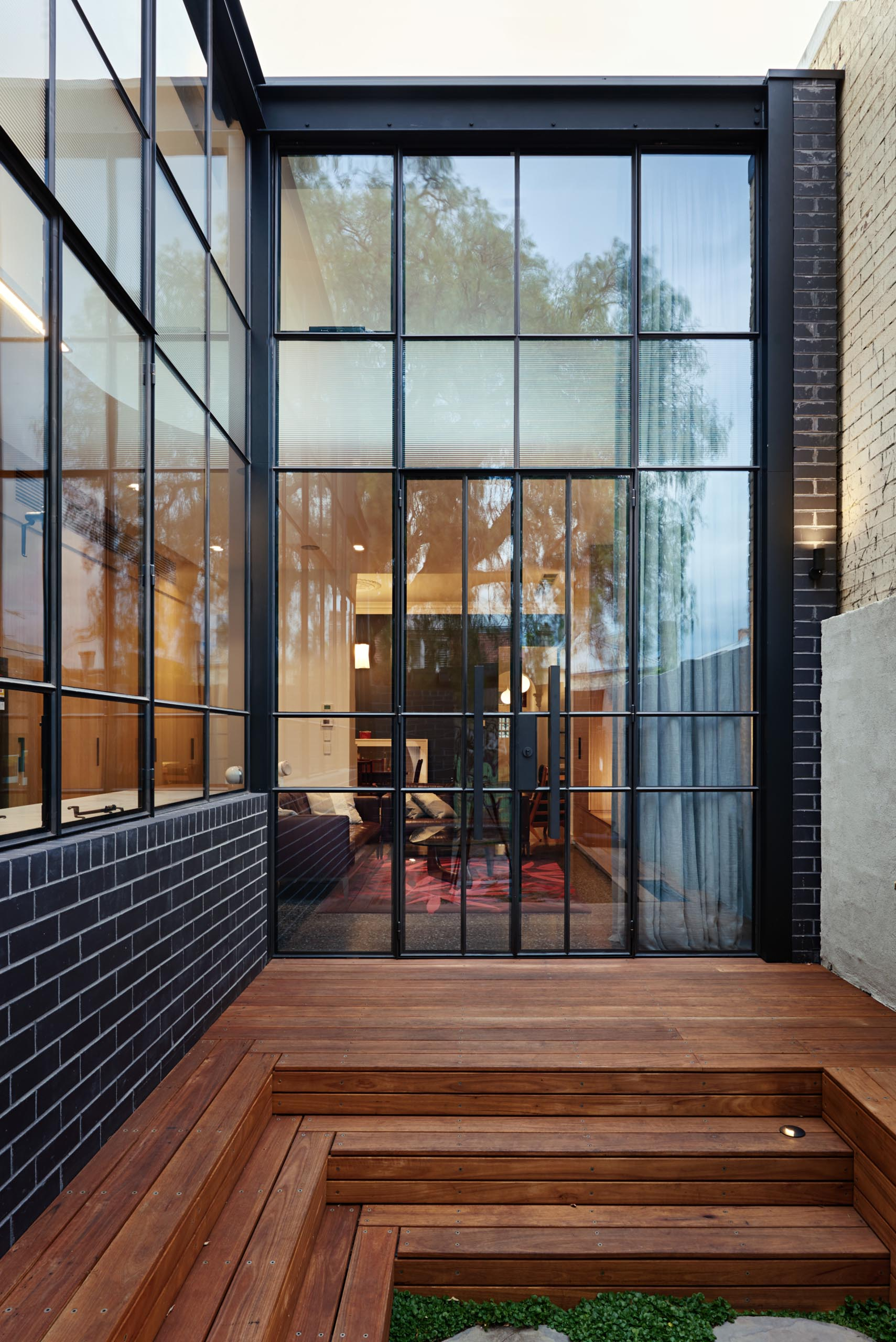 A modern house extension that includes black brick and a black framed glass wall.