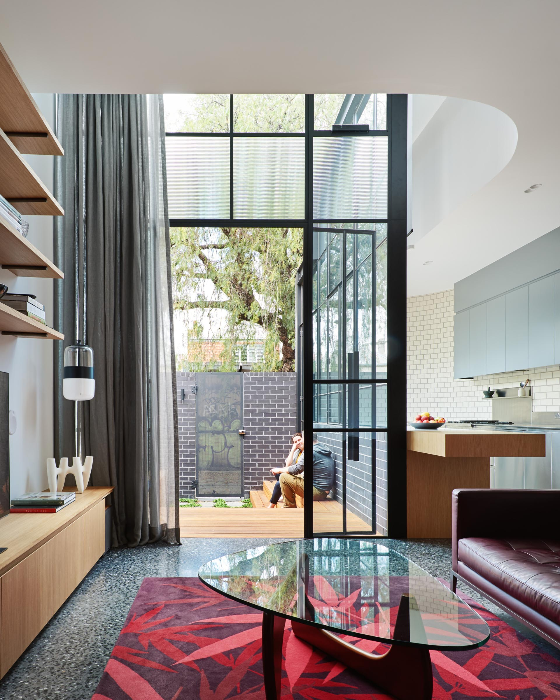 Black blinds and gray curtains can be closed for privacy when needed in this house addition with glass walls.