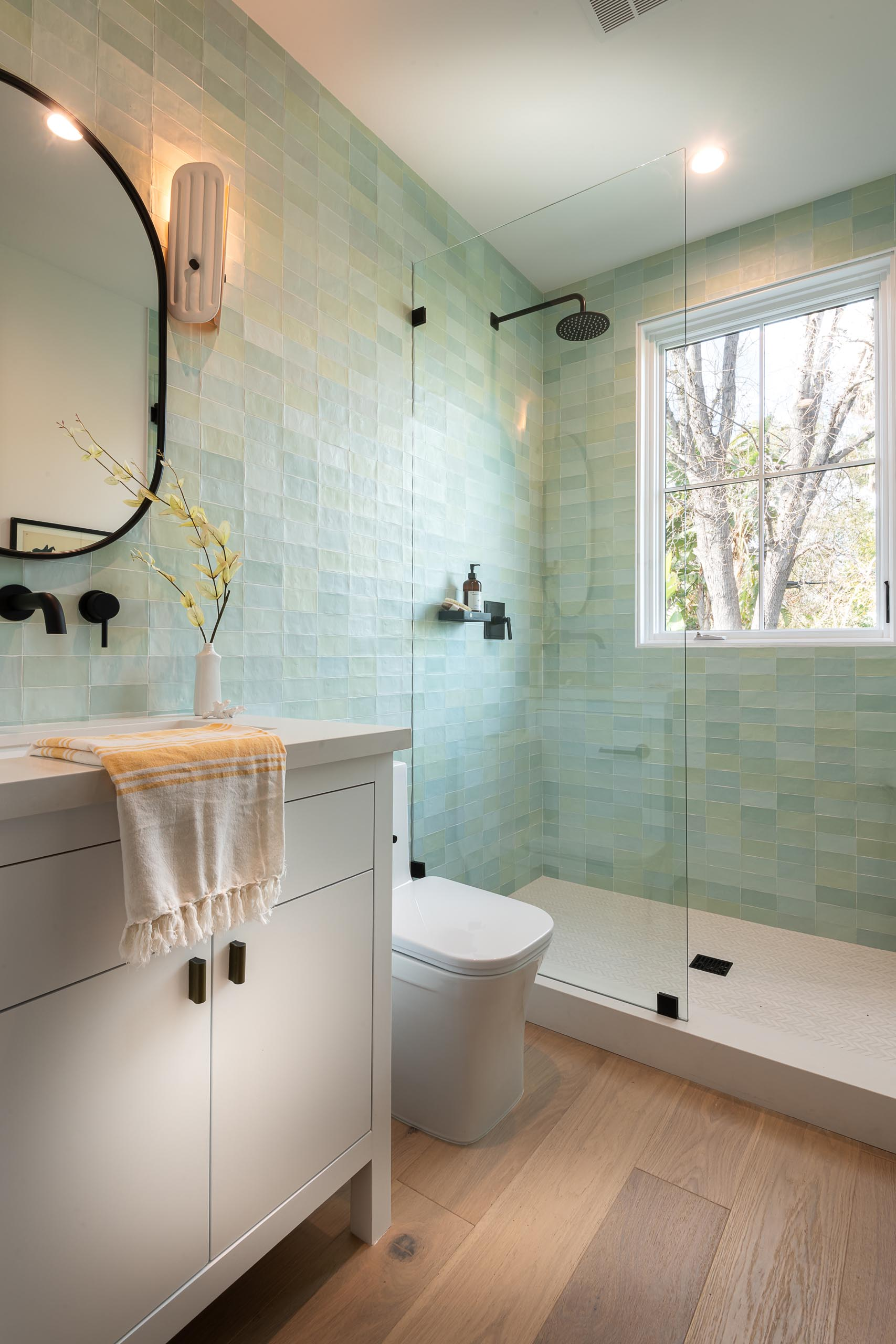 In this bathroom, there's small rectangular tiles in light green and blue tones that cover the walls.