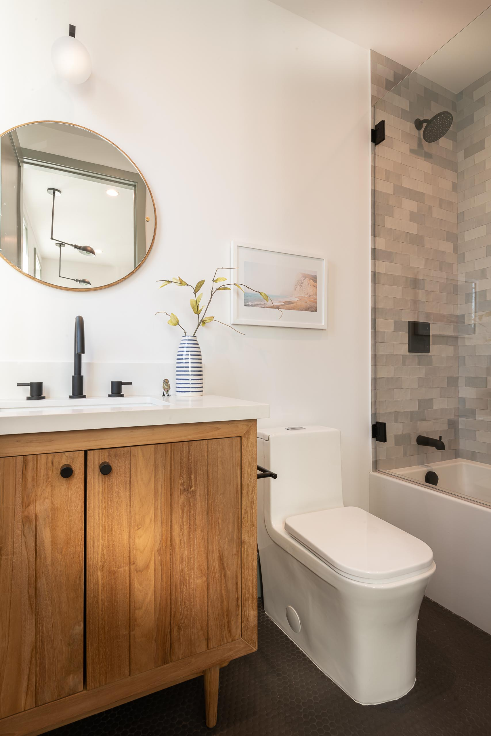 A modern farmhouse bathroom with a rustic wood vanity, round mirror, and black hardware throughout.