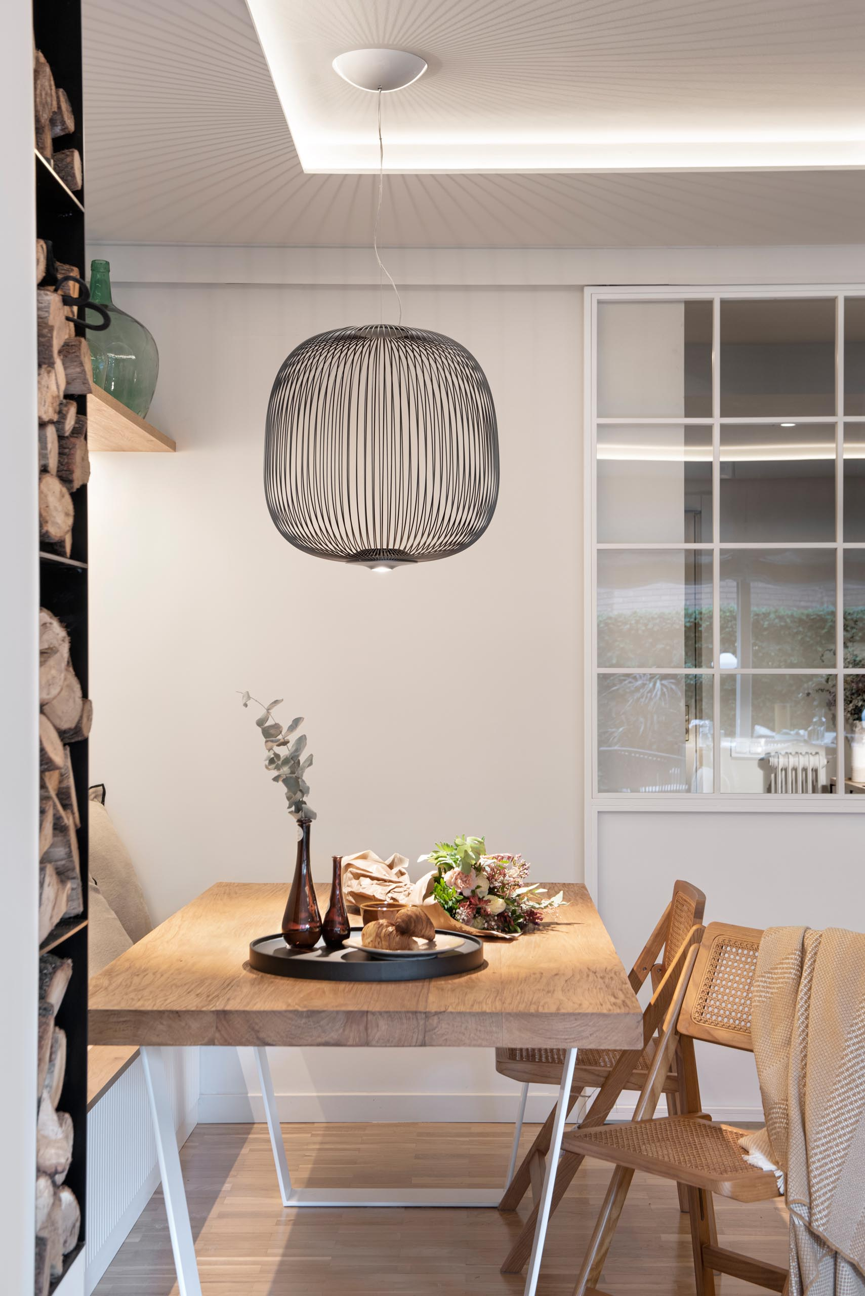 This open plan dining area includes a long bench against the wall, a wood table with wood chairs, a pendant light that gives of lined shadows, and a wood shelf with hidden lighting underneath.