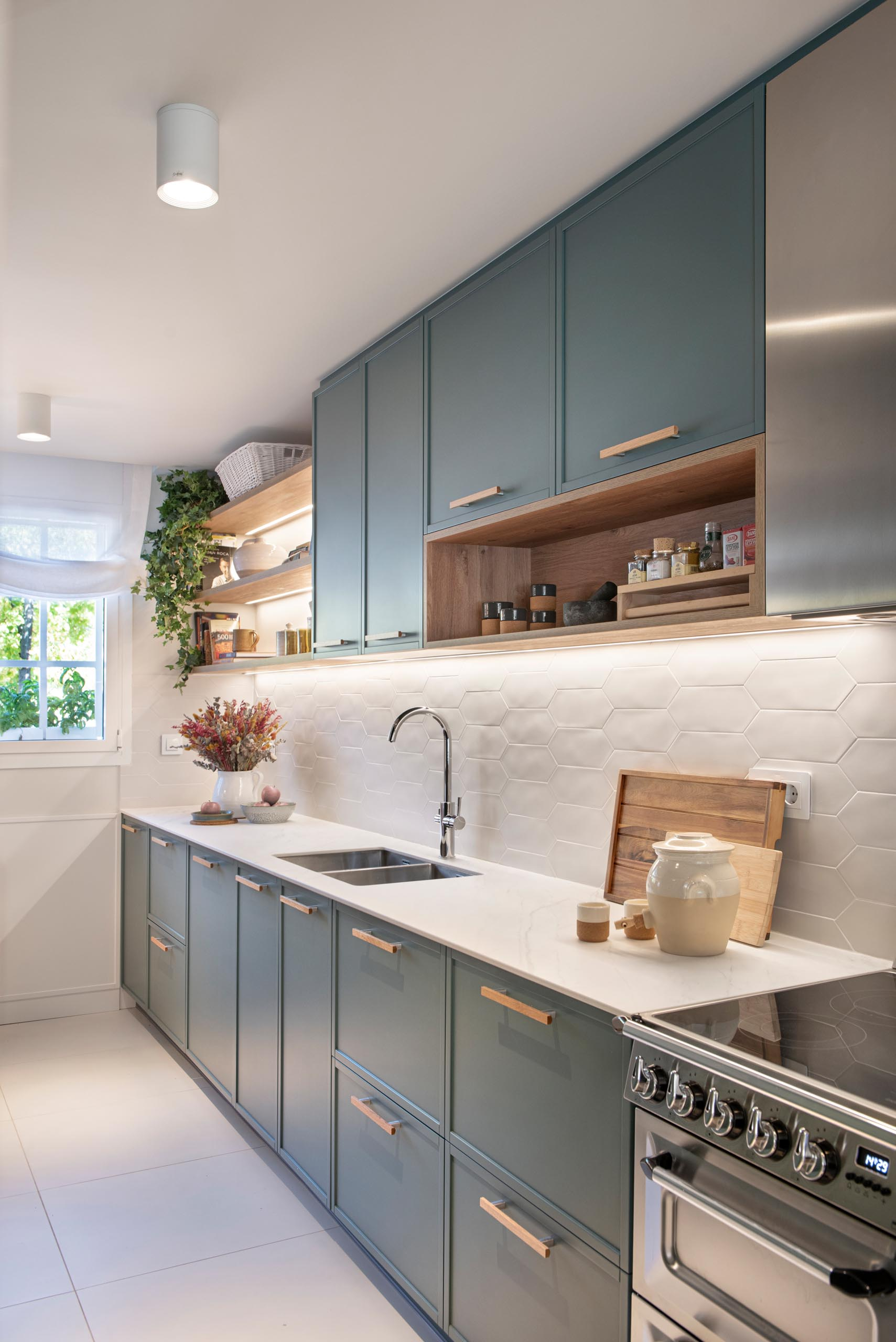 A modern kitchen enclosed within white-framed windows, includes white cabinets that have been paired with a matte green cabinets, while white tiles have been used for the backsplash. An eat-in breakfast nook is tucked into the corner and includes a built-in bench, and a mirrored wall, which makes the space feel larger.