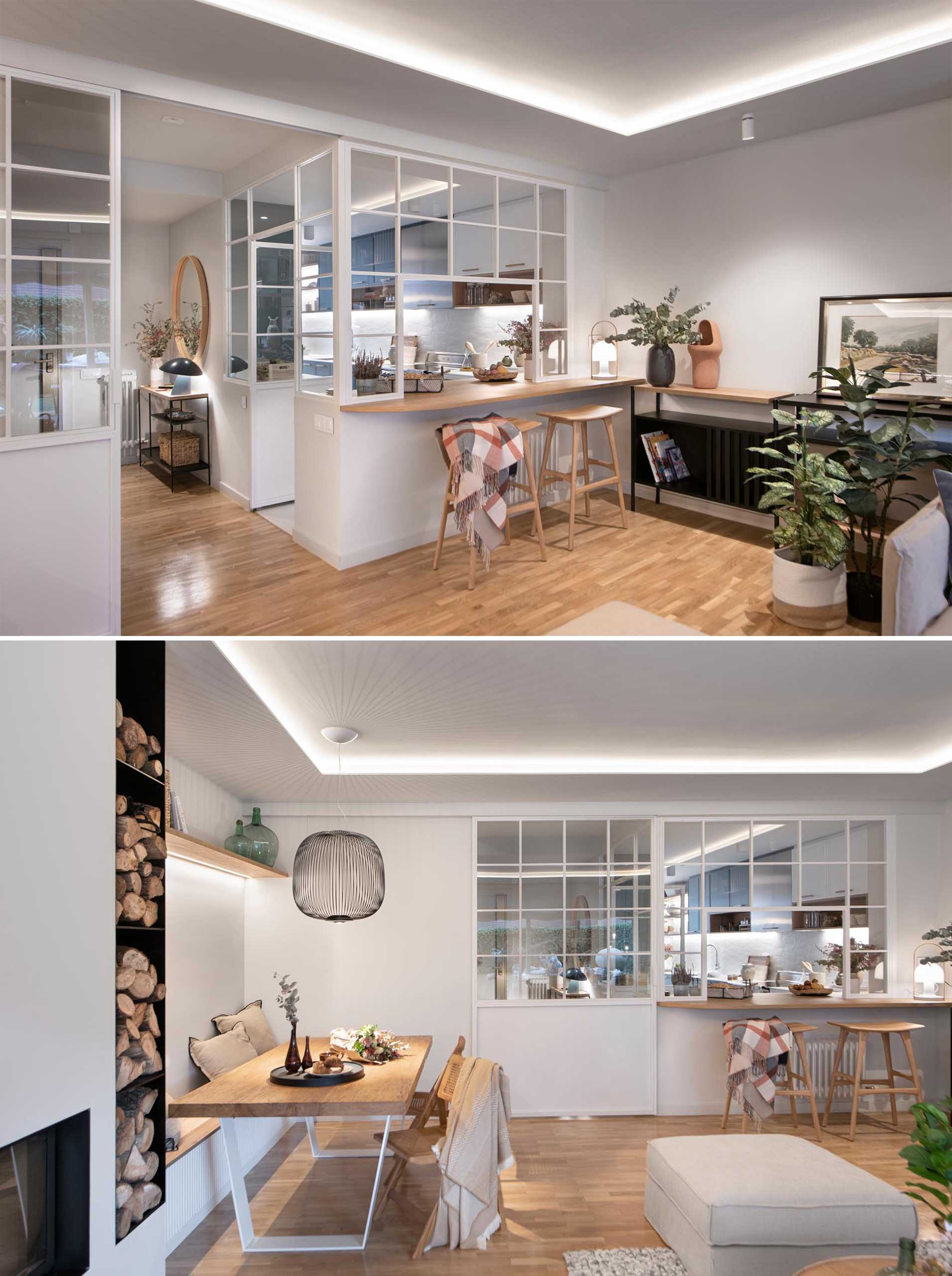 Separating the kitchen from the open plan living room and dining area is a sliding glass door that matches the white window frames of the kitchen walls. There's also a pass-through window with a wood countertop that acts as a bar.