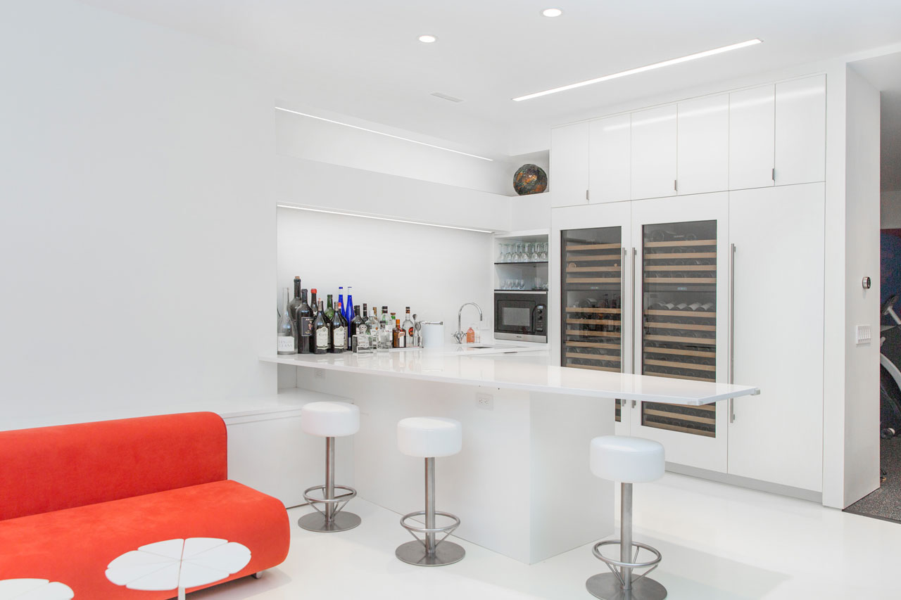 This modern basement bar includes cabinetry has a white lacquer finish, while the white Caesarstone countertop complements the white resin floors.