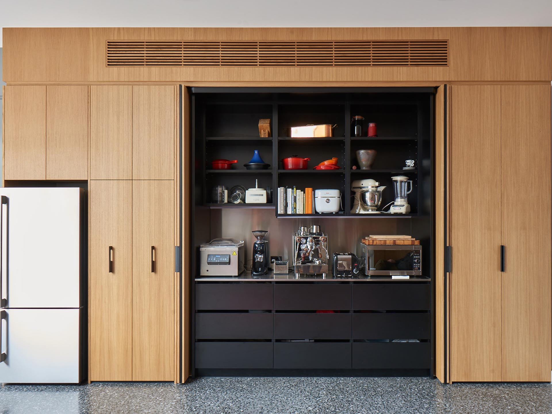 A coffee station is hidden within this modern wood cabinetry, that also includes built-in black shelving and drawers.