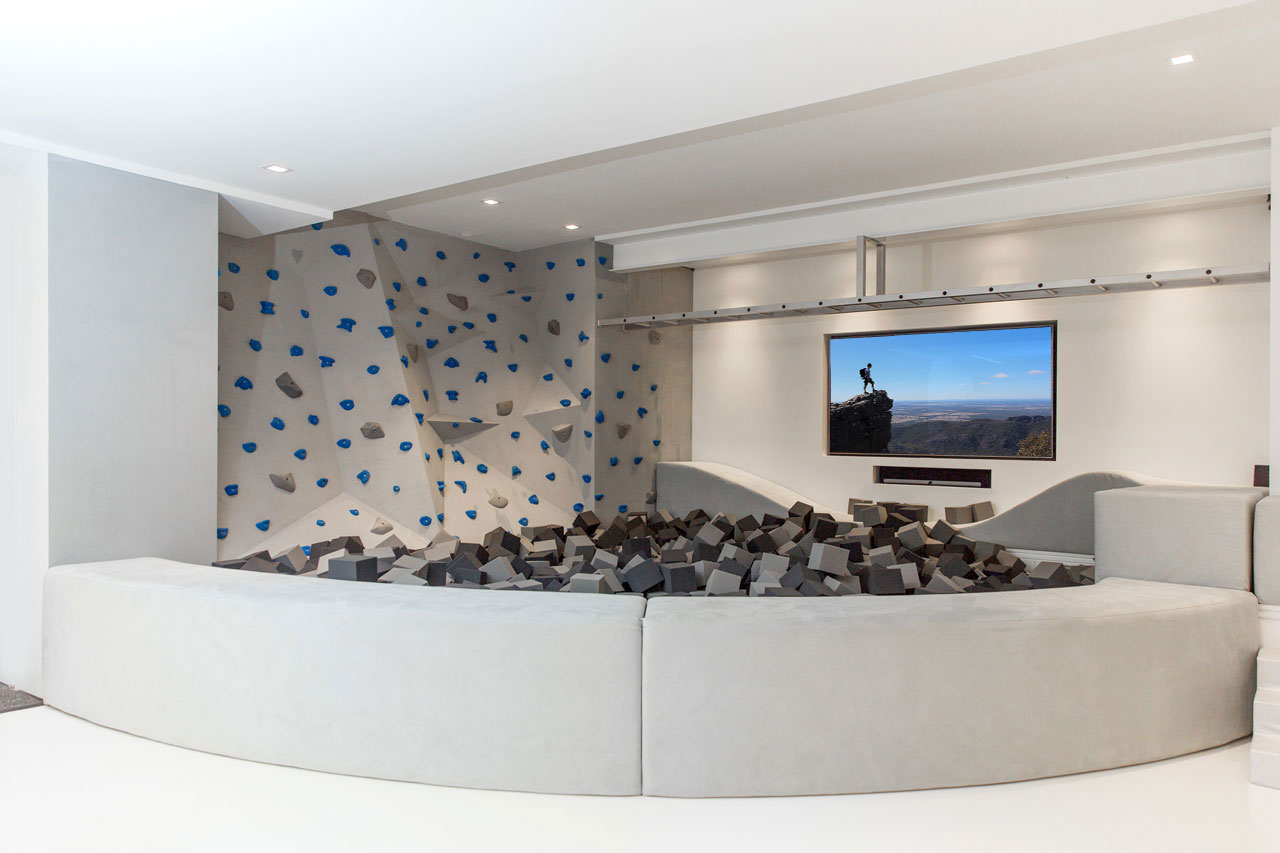 This modern kid's playroom in a basement includes a foam pit area that's defined by a upholstered low wall with a curved shape. This low wall encloses the foam pieces, which act as a soft area to land, should a child fall or jump from the rock climbing wall or monkey bar.