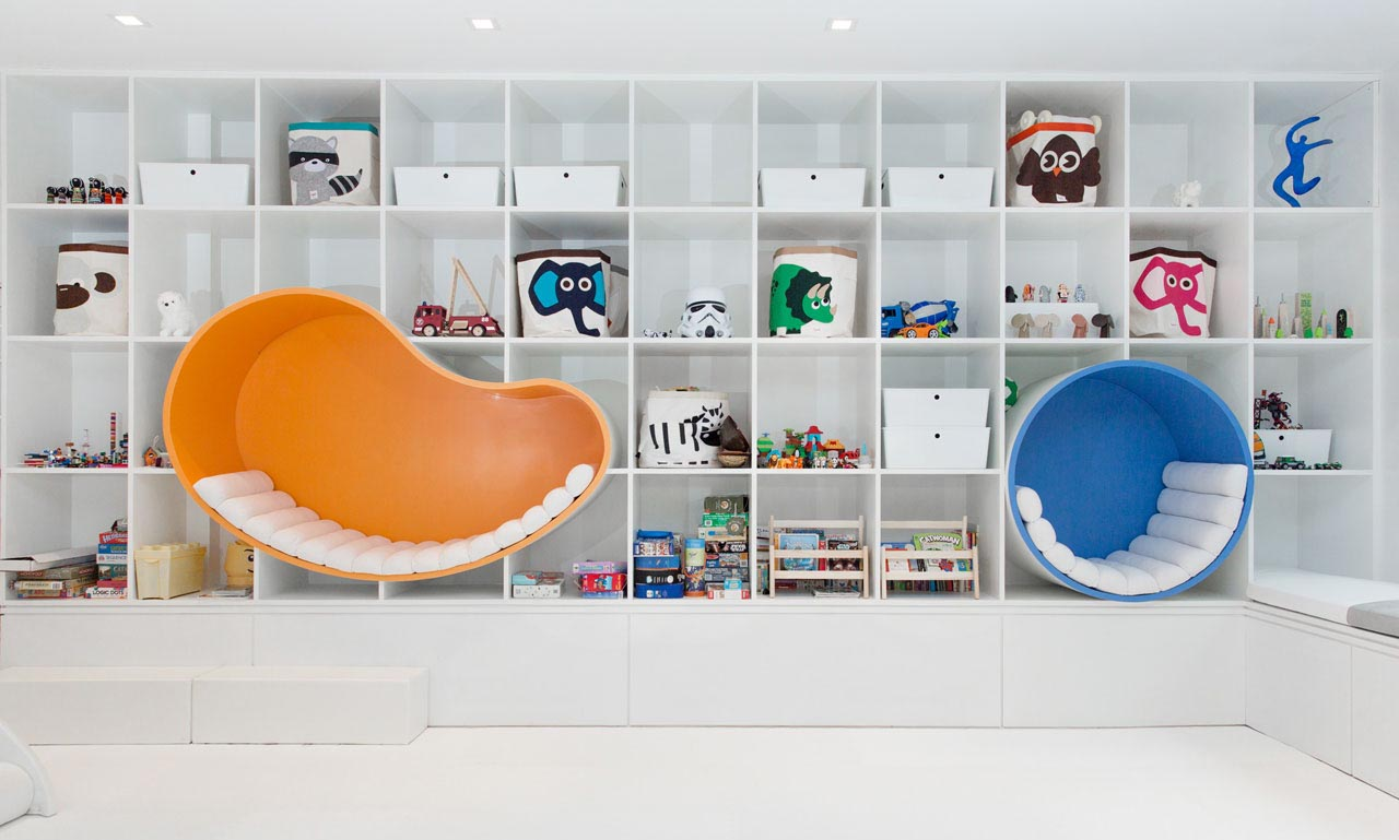 A wall of storage with square shelves provides plenty of storage for the space, while bright and colorful seating nooks are lined with padded cushions.