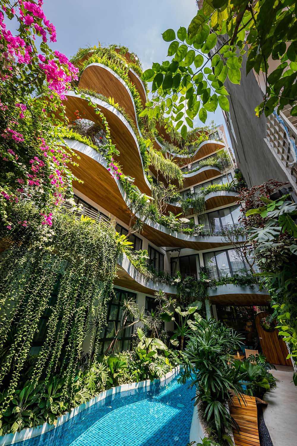 A modern building with curved balconies and overhanging plants.