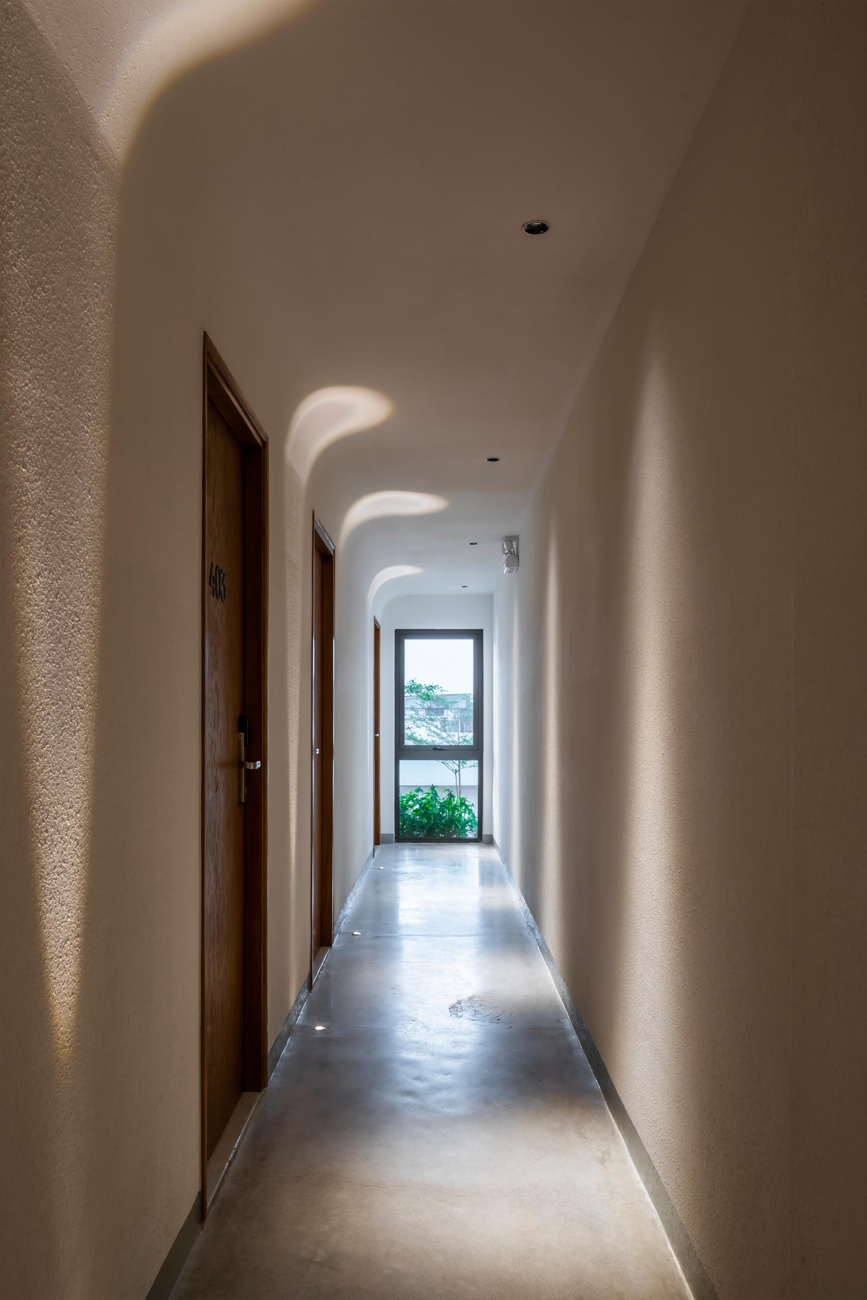Bright hallways with lighting embedded in the concrete floors, and in the ceiling, guides guests to their private apartments.
