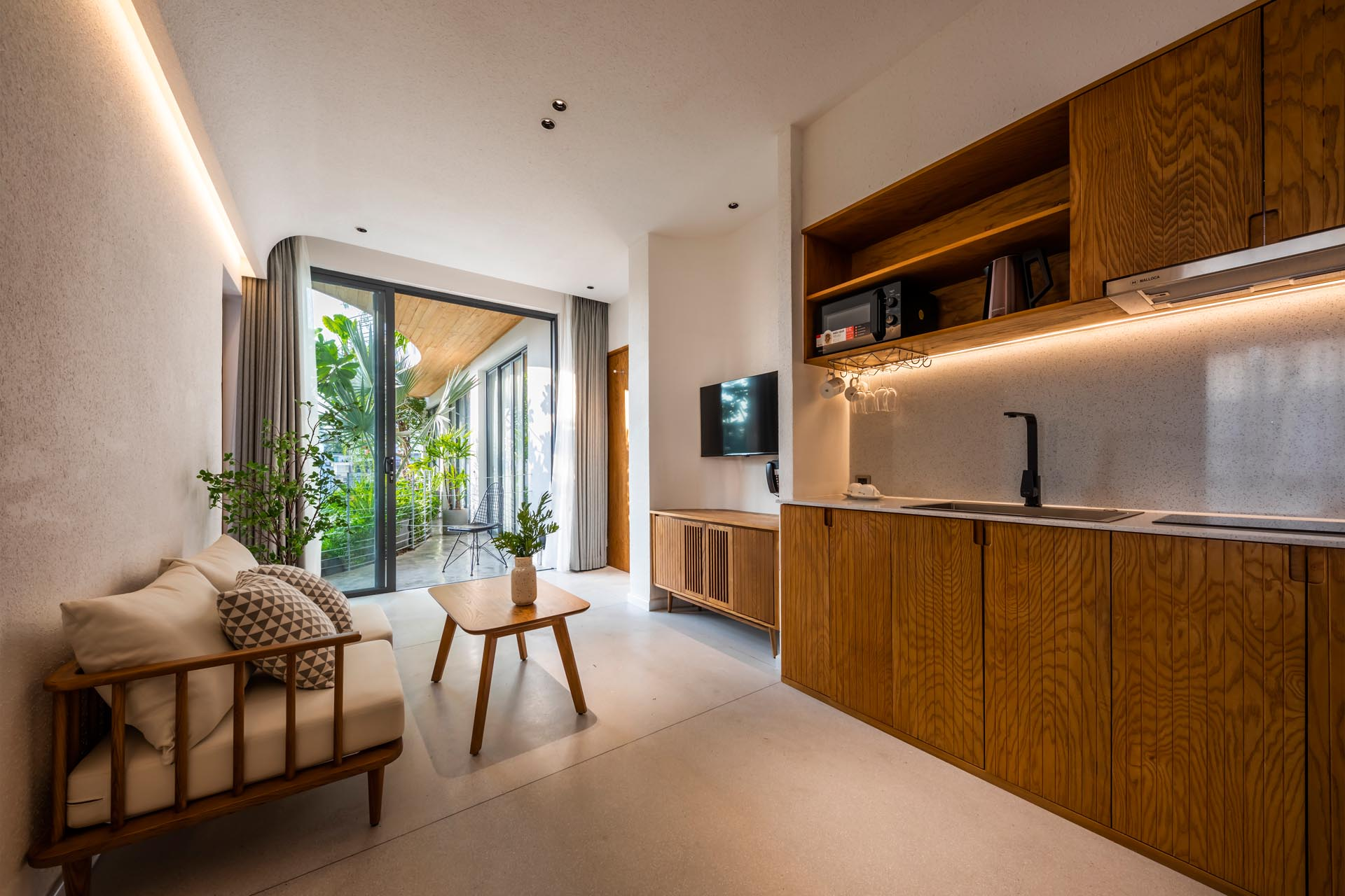 A minimalist apartment interior with LED lighting, a small living room, and kitchenette.