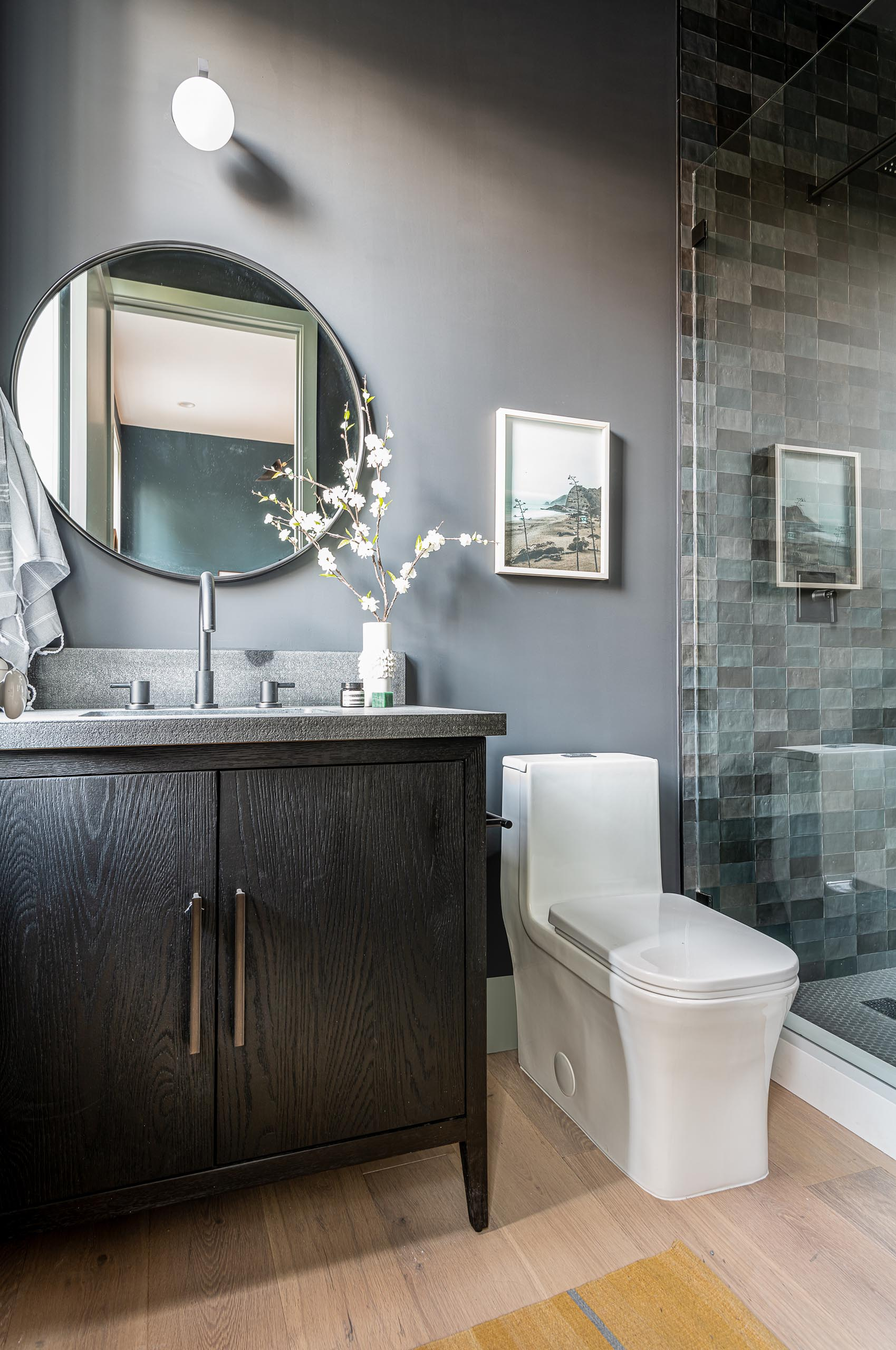 A modern bathroom with light gray walls, a round mirror, and a dark wood vanity.