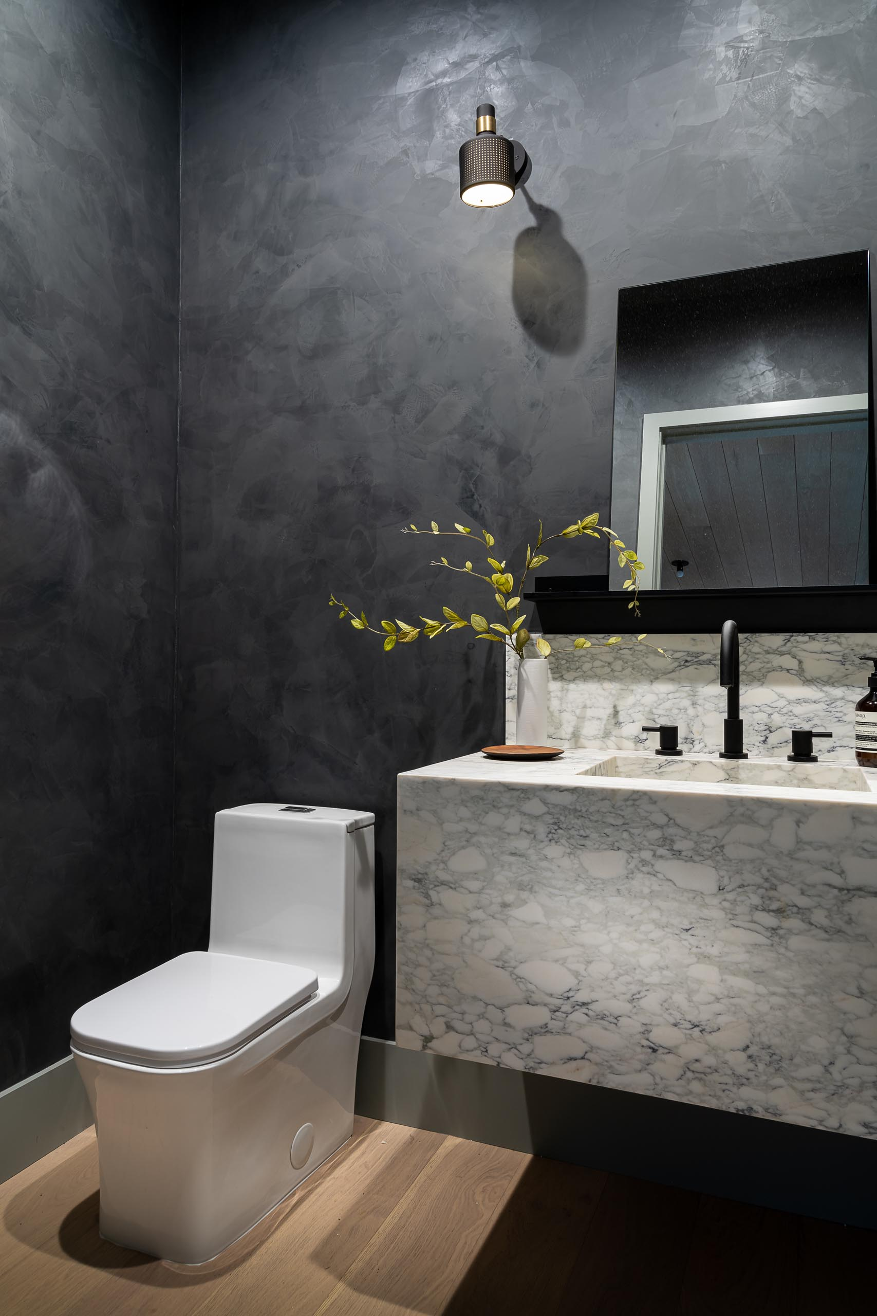A modern bathroom with dark gray walls helps to create a dramatic look.