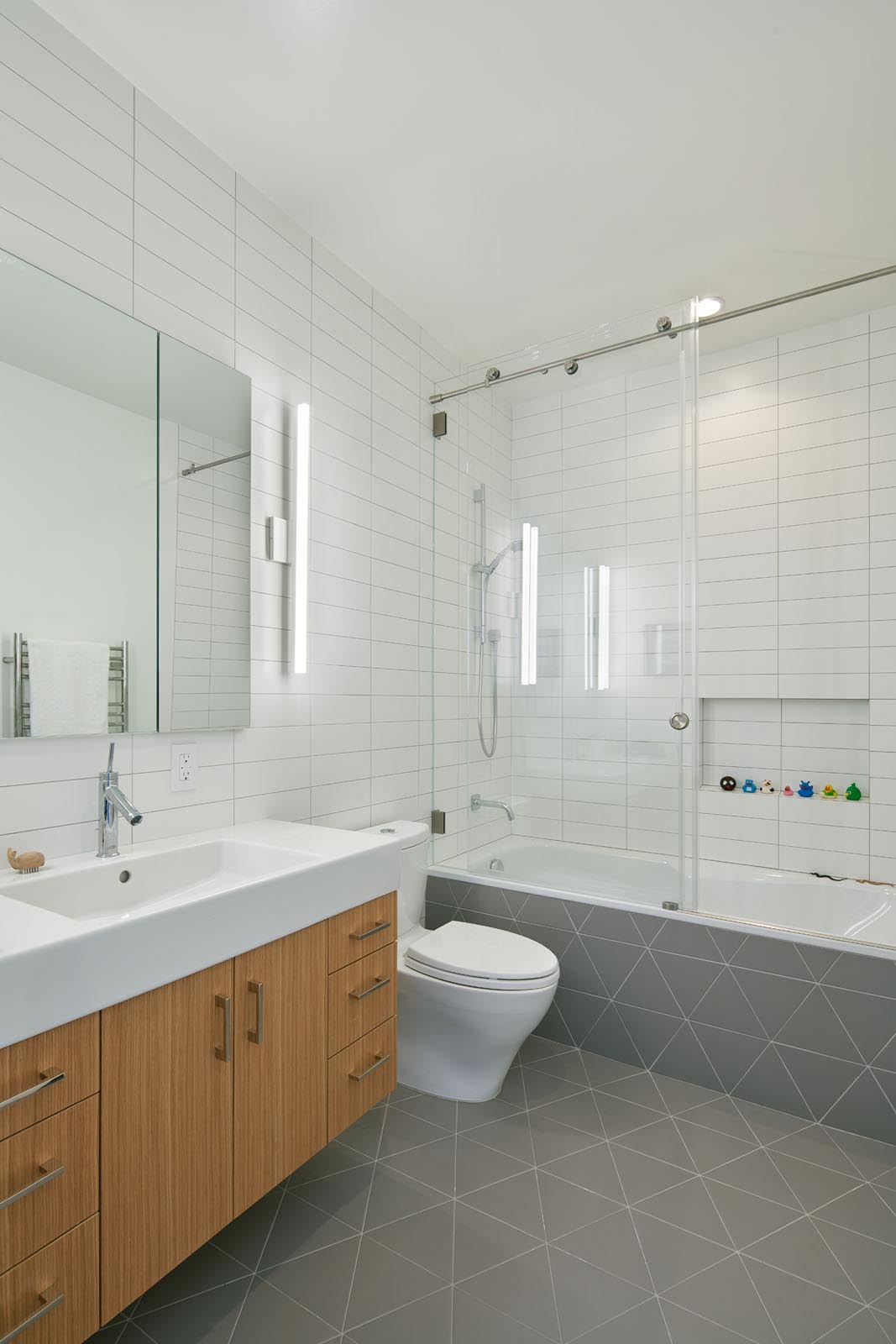 In this modern bathroom, simple white rectangular tiles cover the walls, while gray triangle tiles cover the floor and wrap onto the bathtub.