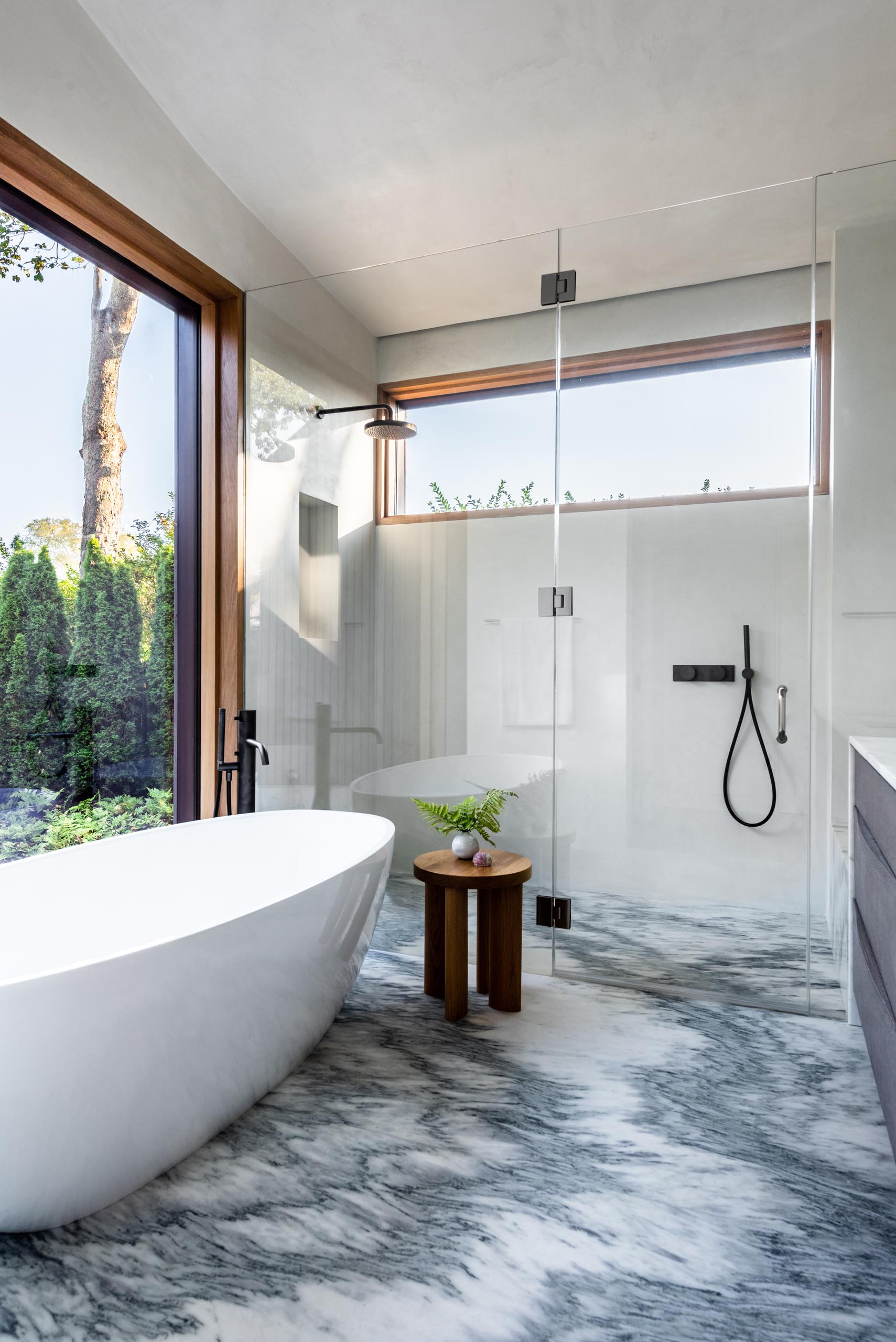 In this modern bathroom, an eye-catching floor complements the white freestanding bathtub and black bathroom hardware.