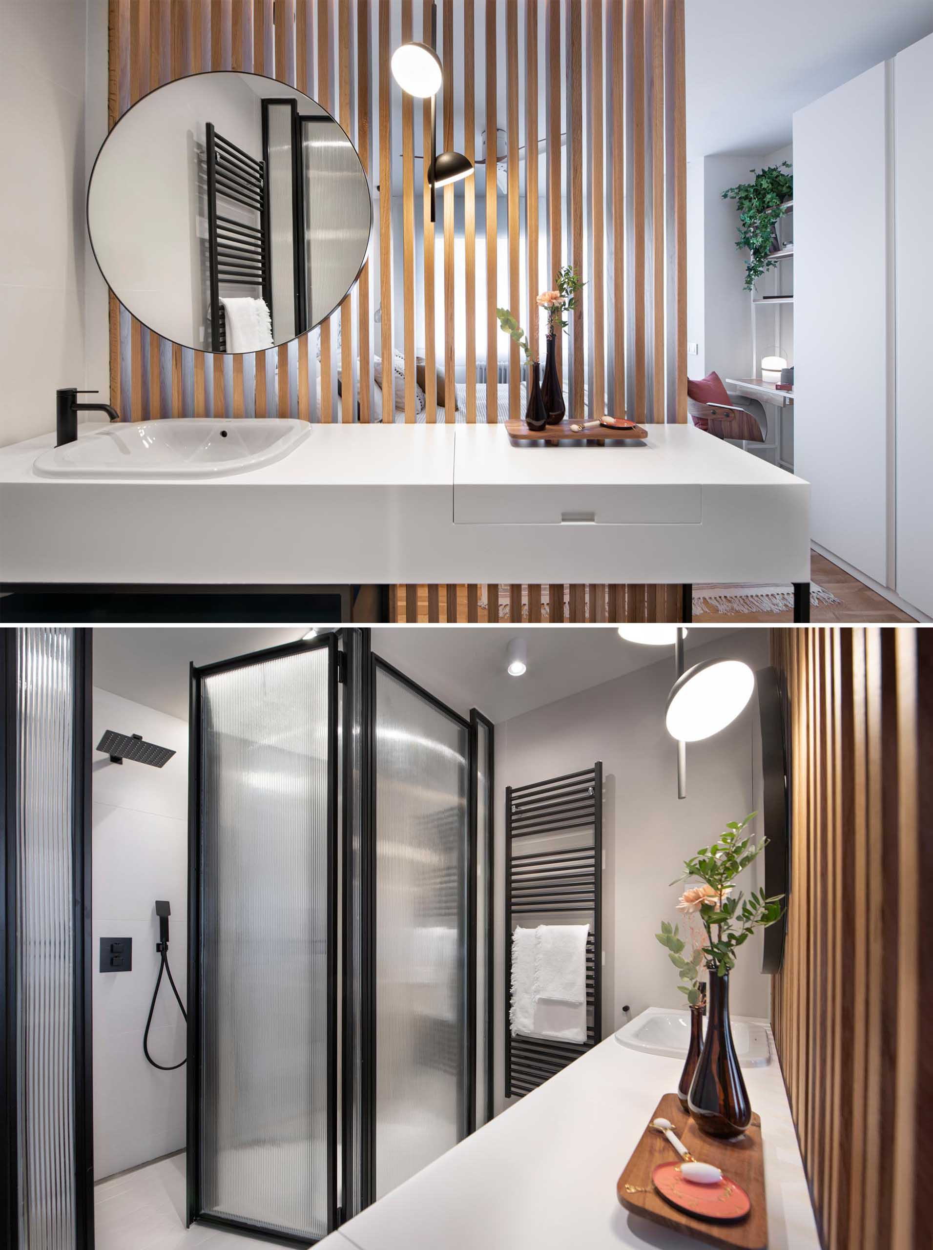 This en-suite bathroom is separated from the bedroom by a wood slat wall, while black framed glass walls hide the shower and toilet, and the vanity has a thick white countertop that hides a makeup area.