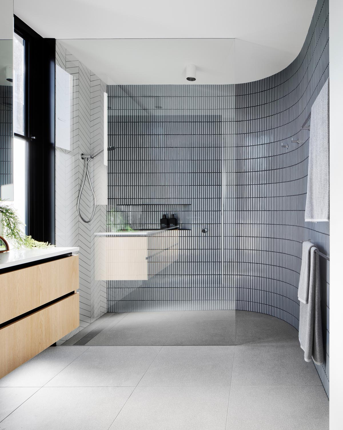 In this modern bathroom, there's two types of tiles that cover the walls in the shower, with a white tile in a chevron pattern, and a small gray tile laid in a vertical pattern.