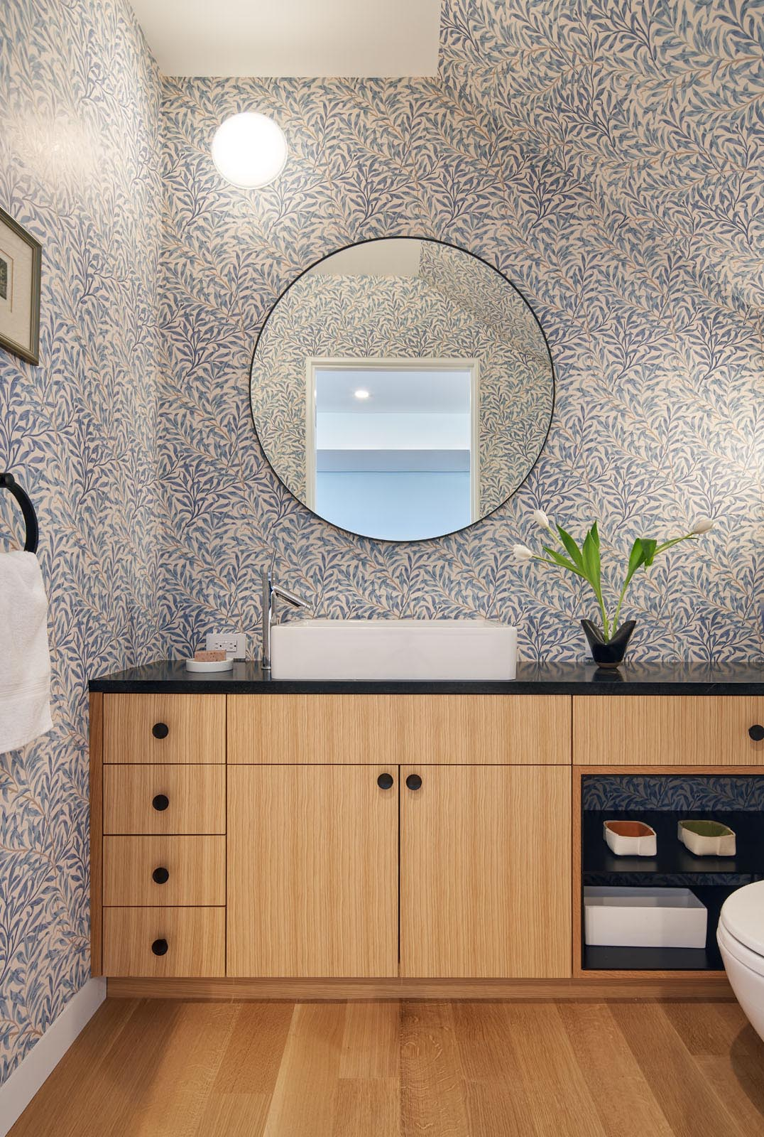In this modern bathroom, the walls are covered in a wallpaper with a leaf design, while a round mirror hangs above a wood vanity with a black countertop.