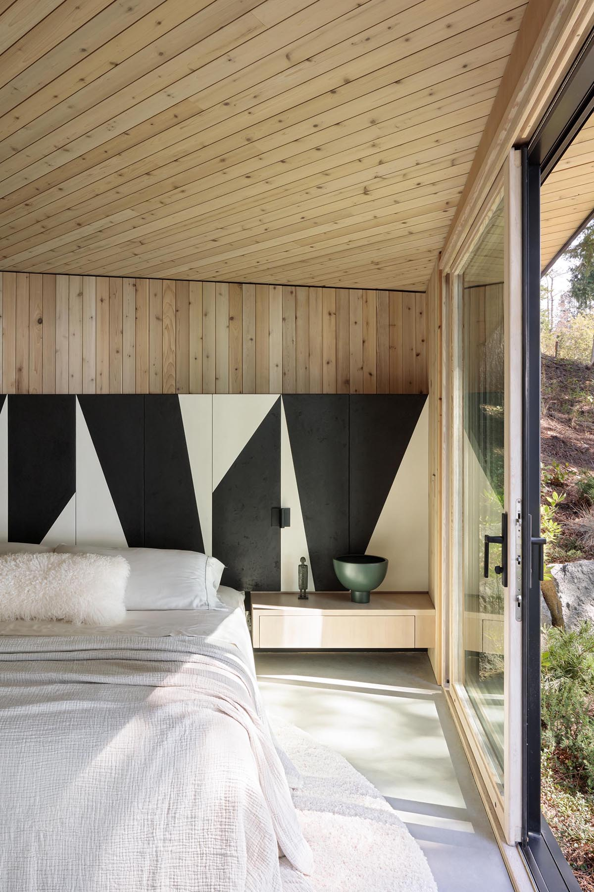 This modern bedroom makes the most of the view by having a wall of windows, while a black and white partial accent wall wraps around the room, and adds an artistic element to the space.