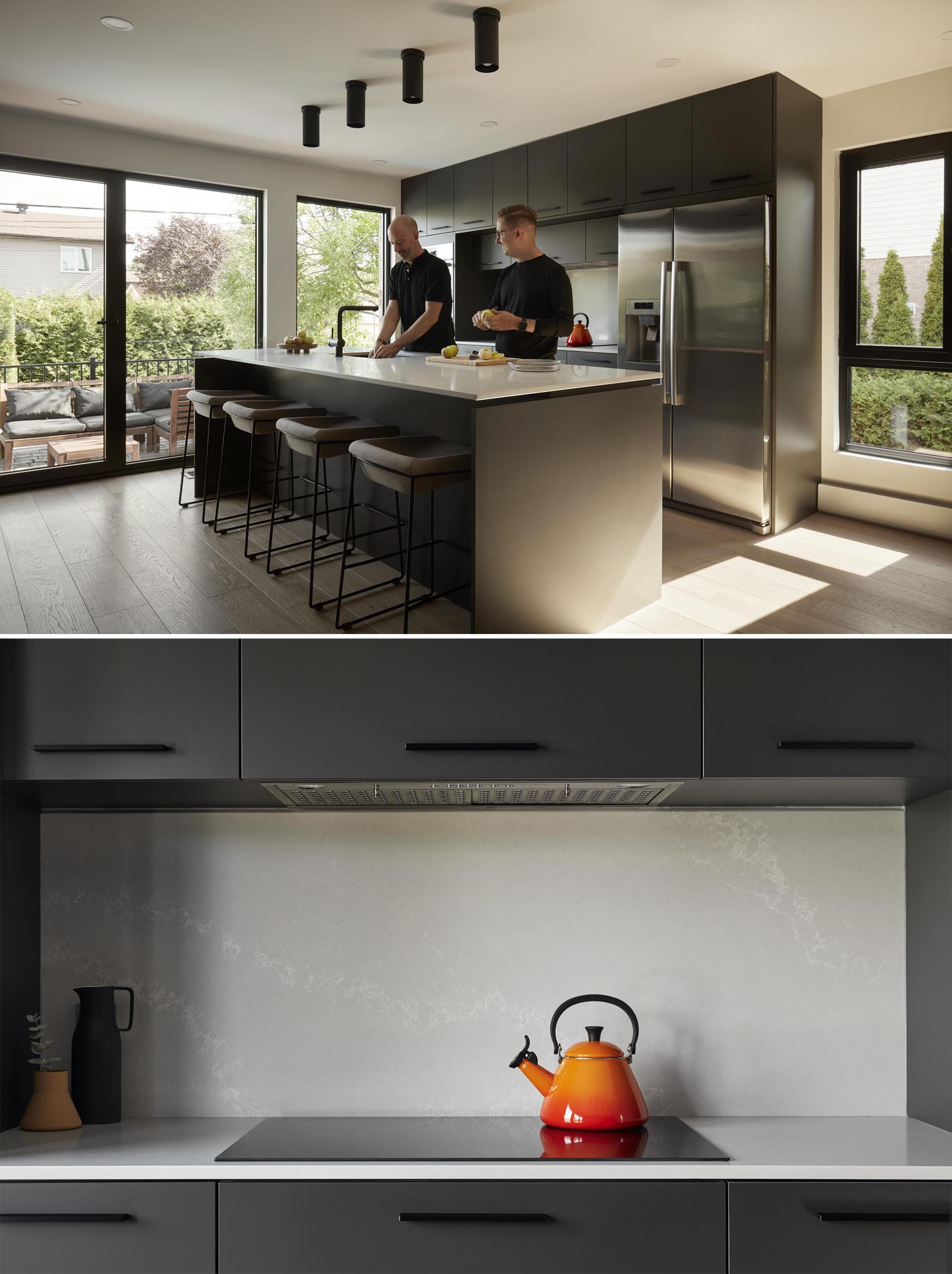 In this modern kitchen, two large blocks of integrated built-in cabinets face each other, with an island positioned between them.