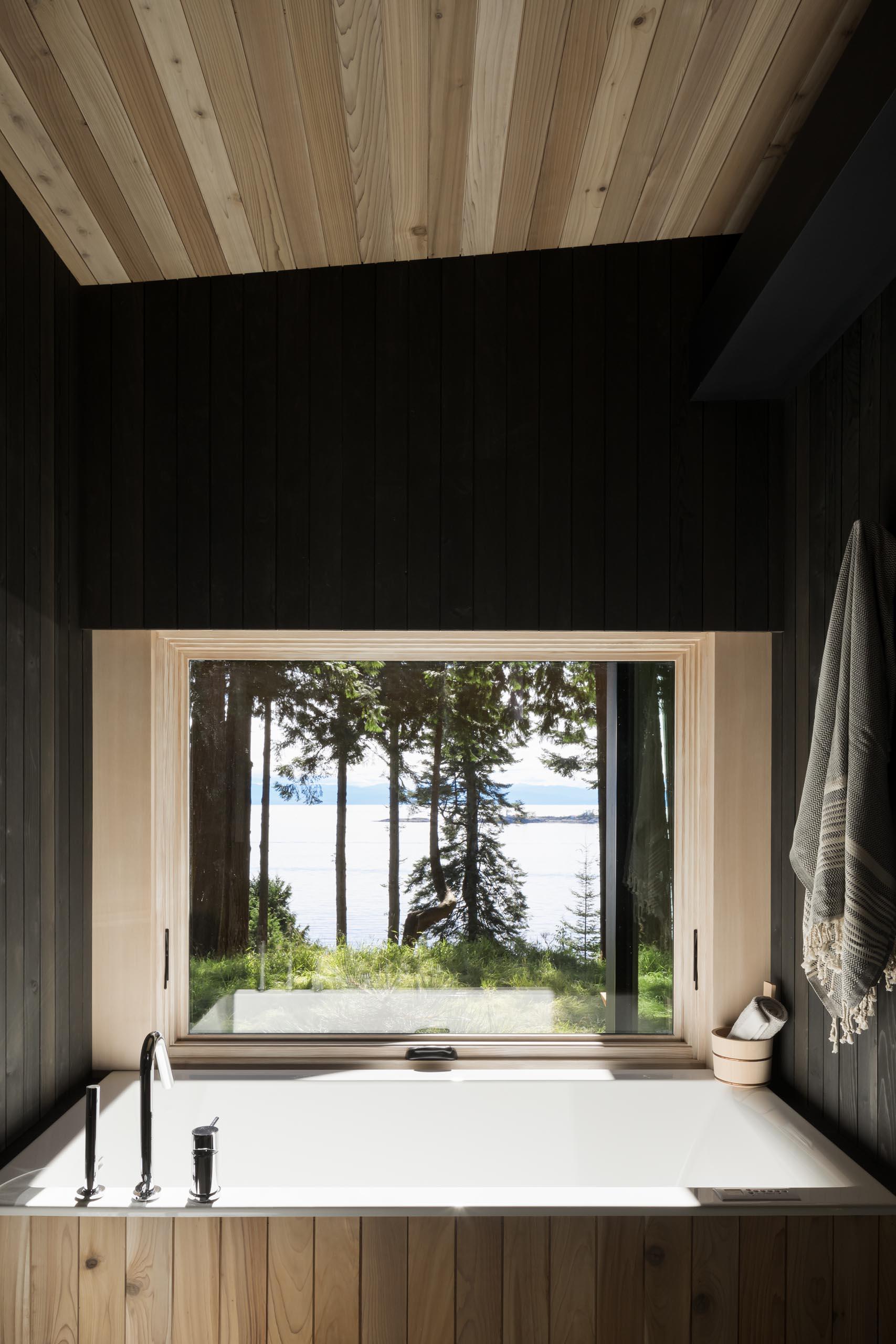 In this modern bathroom, blackened cedar wood walls surround a built-in bathtub.