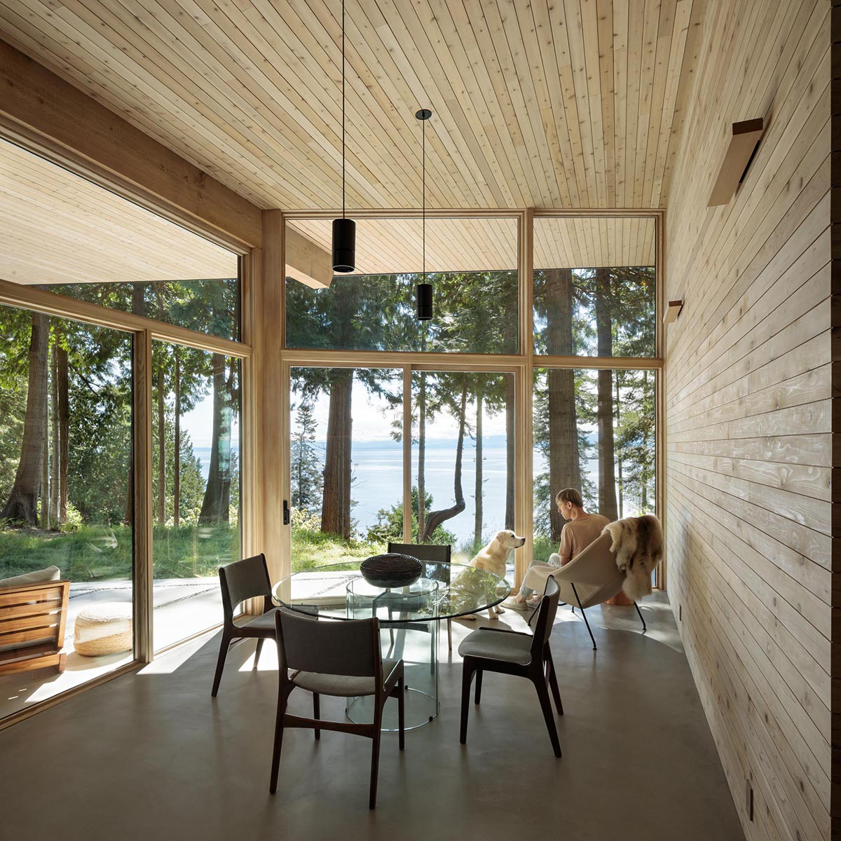 Adjacent to a patio with a fire bowl is the dining room, which has a wood lined wall, and a concrete floor.