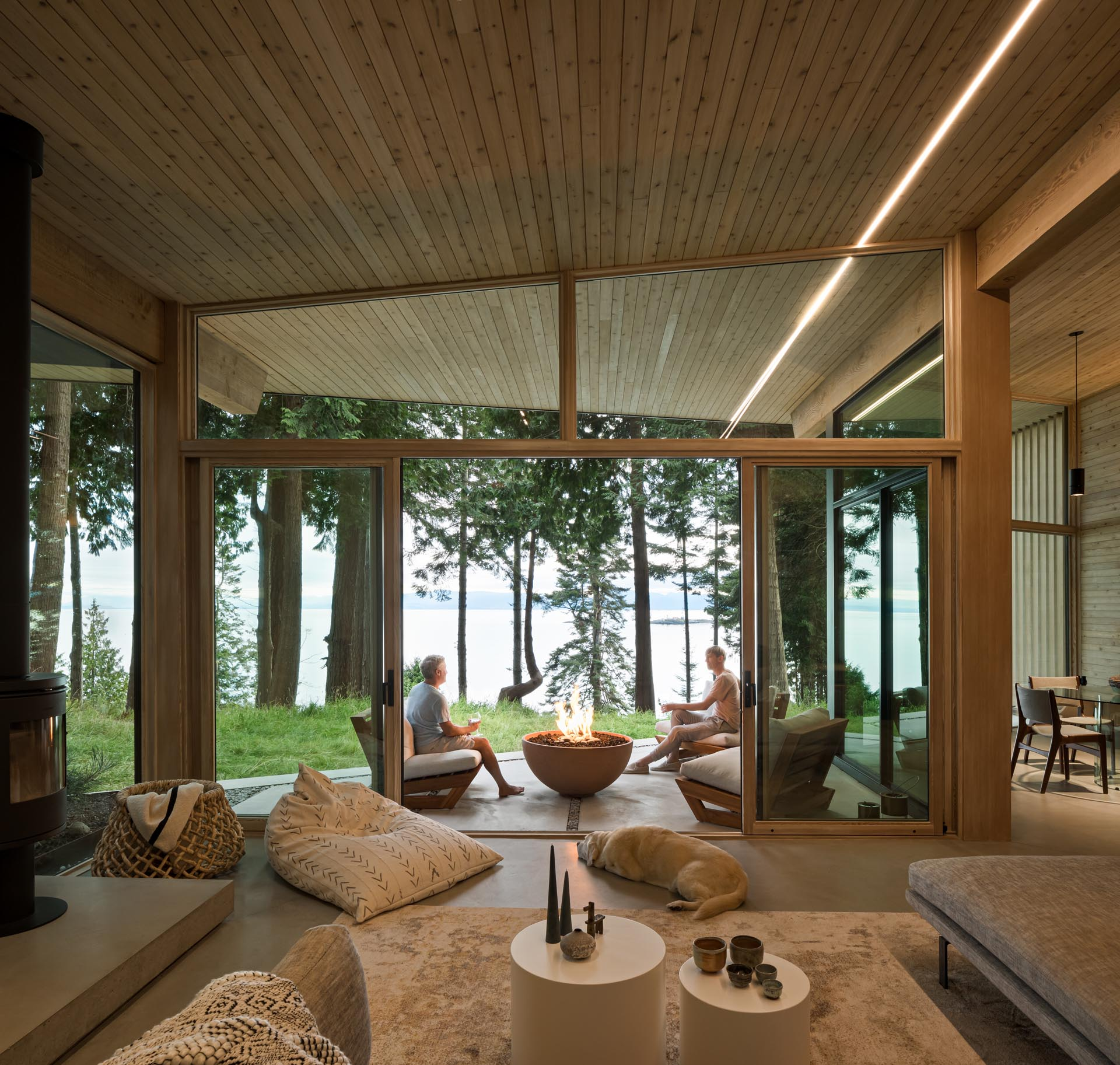 A wall of glass with sliding doors connects the living room to a covered patio that's furnished with chairs and a fire bowl, and has water views.