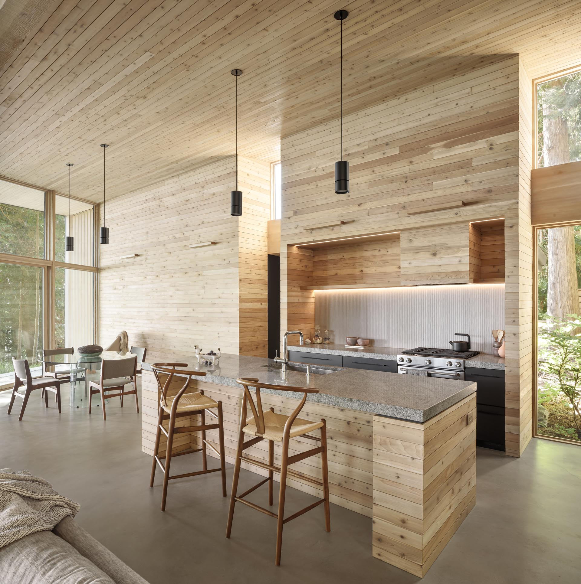 This modern kitchen lined with cedar,  has been designed with thick countertops, and dark lower cabinets.