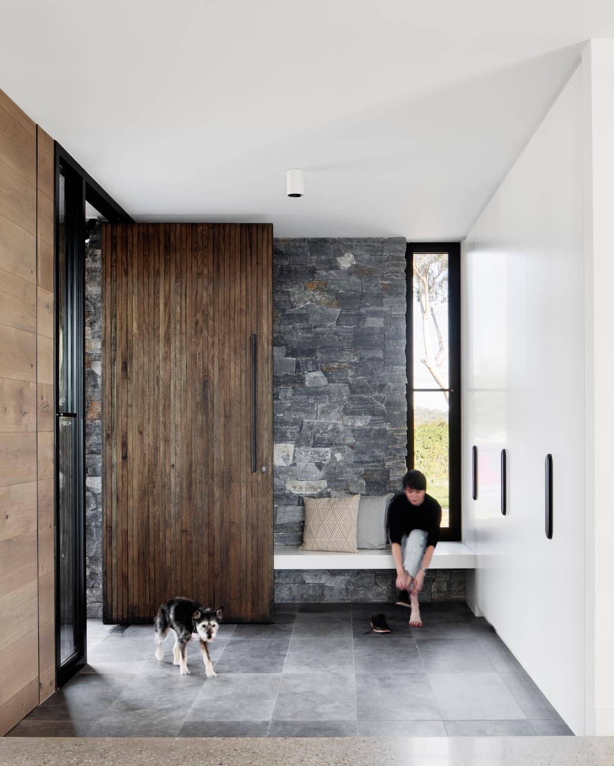 A large front door with dark vertical wood welcomes visitors to the home, with the stone wall continuing through the interior. A wall of floor-to-ceiling white cabinets provides plenty of storage, while a bench creates a place to take shoes off.