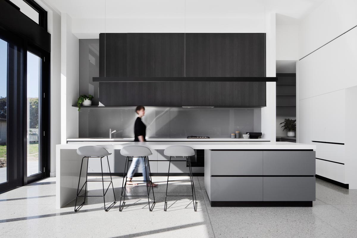 In the kitchen there's a large island with room for seating, and a minimalist linear pendant light hanging above.