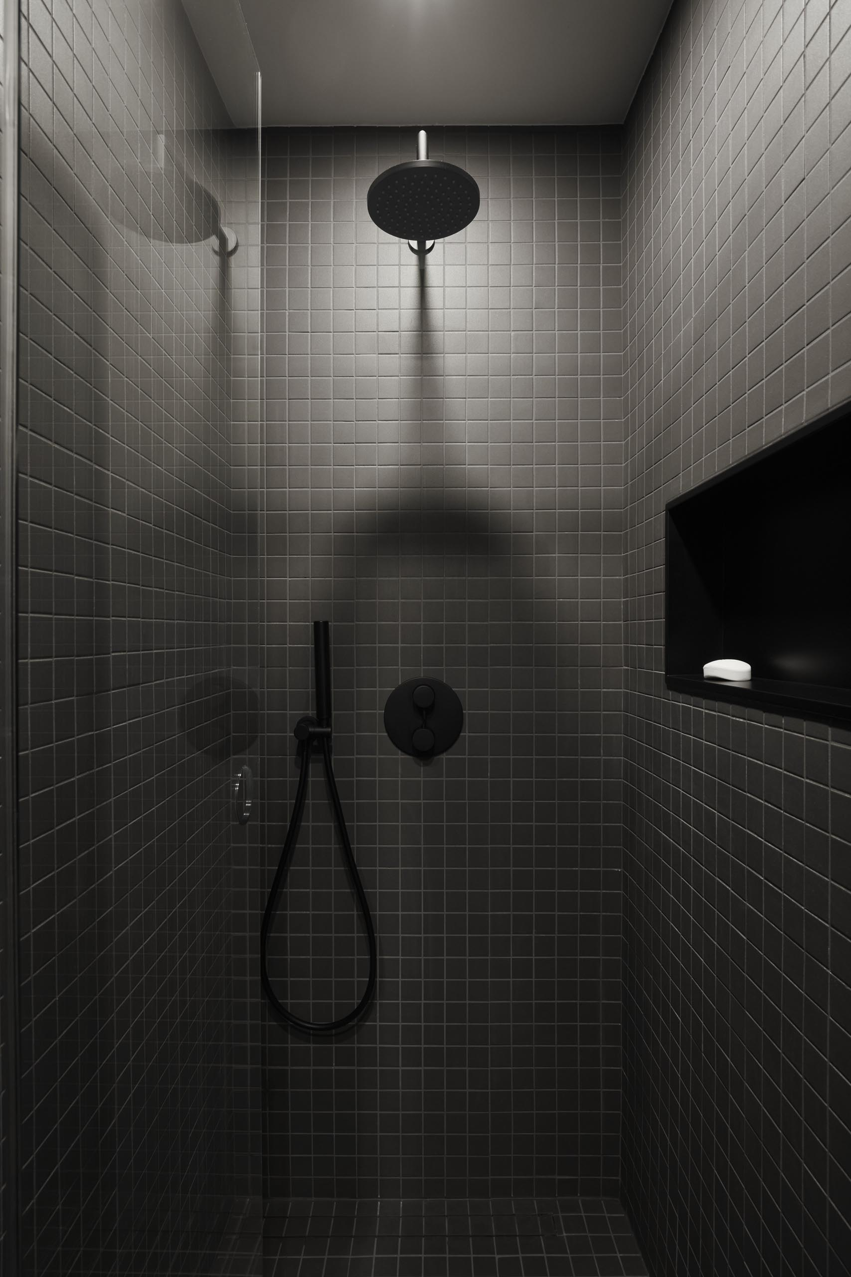 A modern shower with square gray tiles, black hardware, and a shelving niche.
