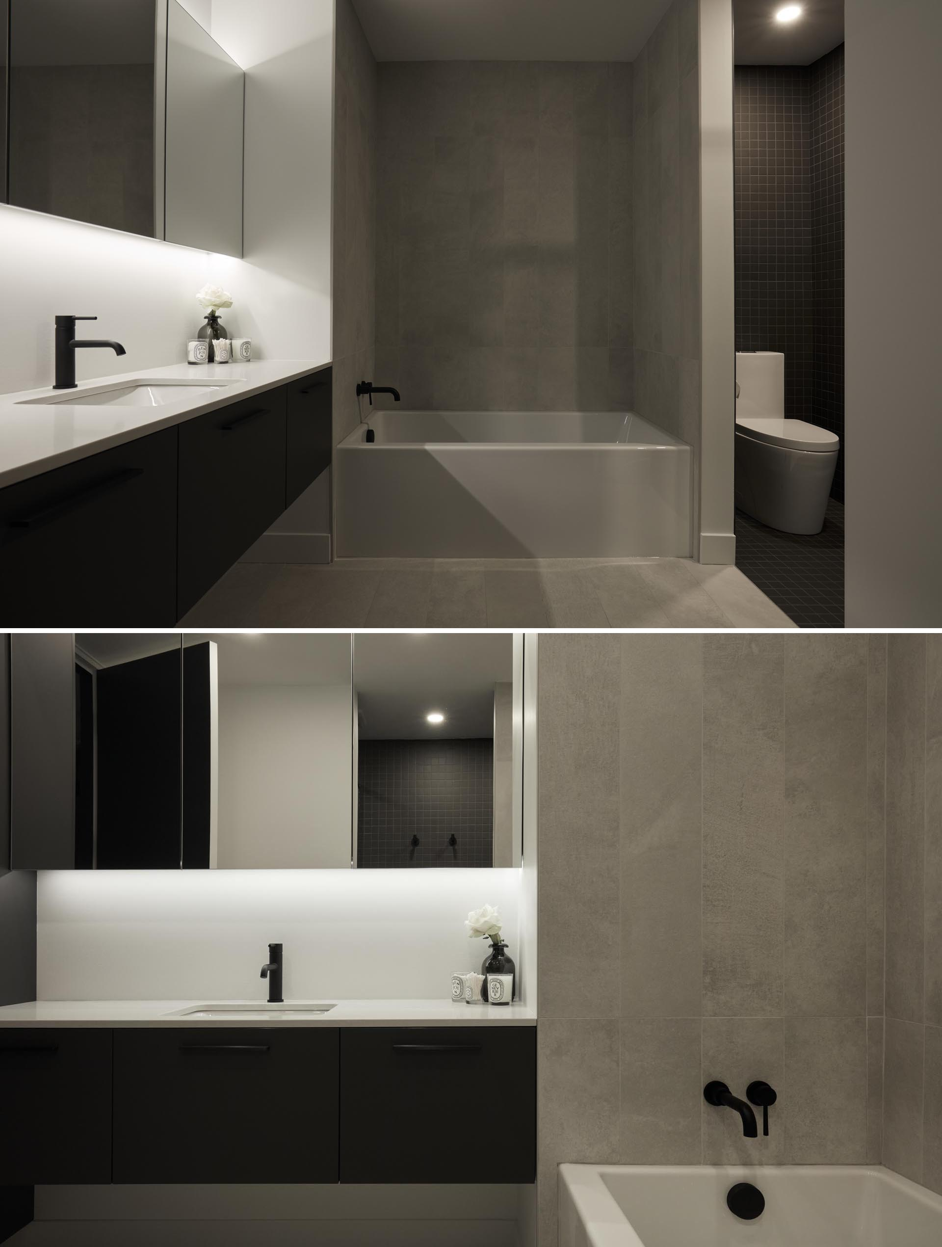 The design of this modern bathroom has been separated into zones. The light zone combines the vanity, the medicine cabinet, and the bath, while the dark zone combines the toilet and a shower with built-in shelving niche.