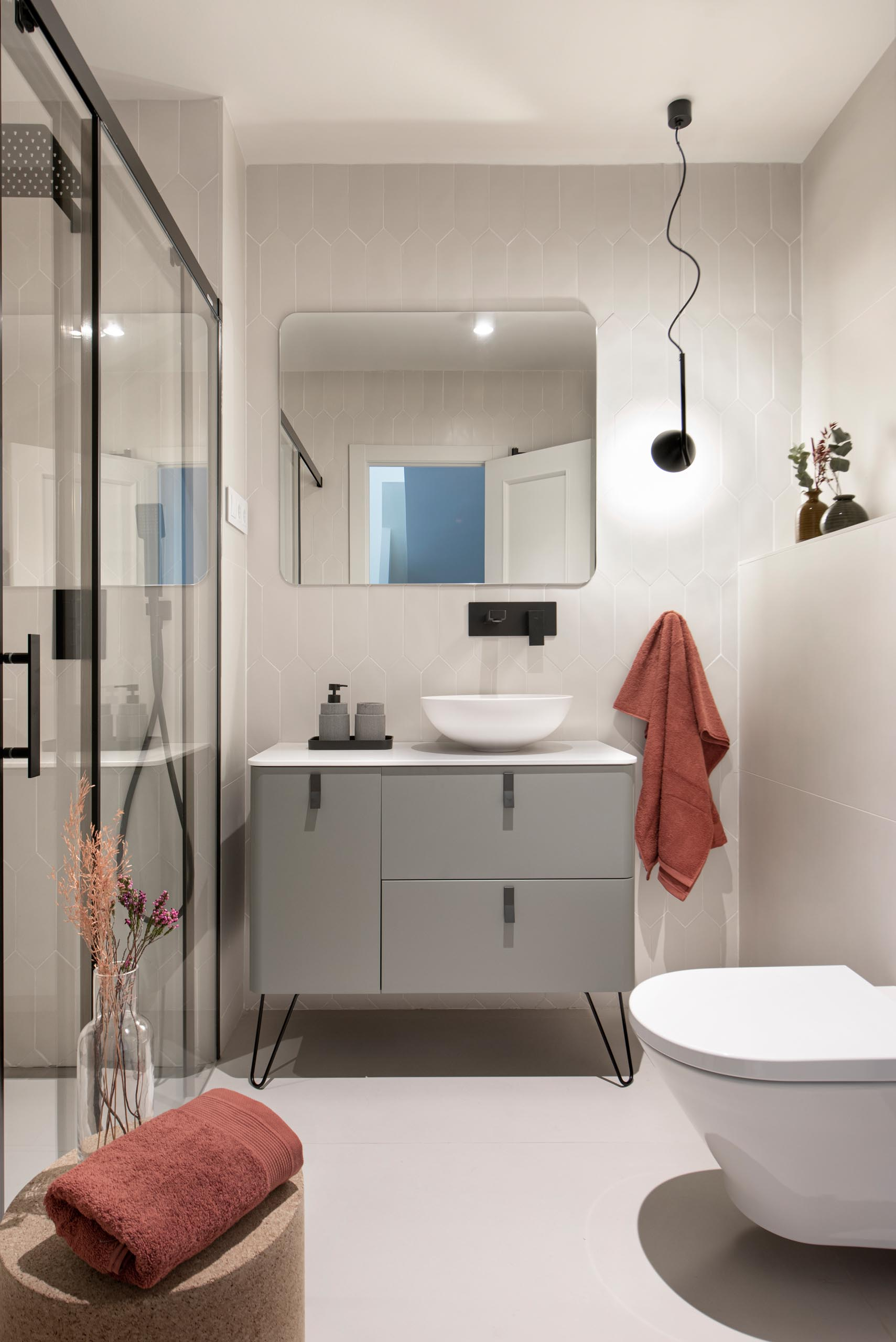 This modern guest bathroom has a simple neutral color palette with a gray vanity, light gray tiles, and black accents.