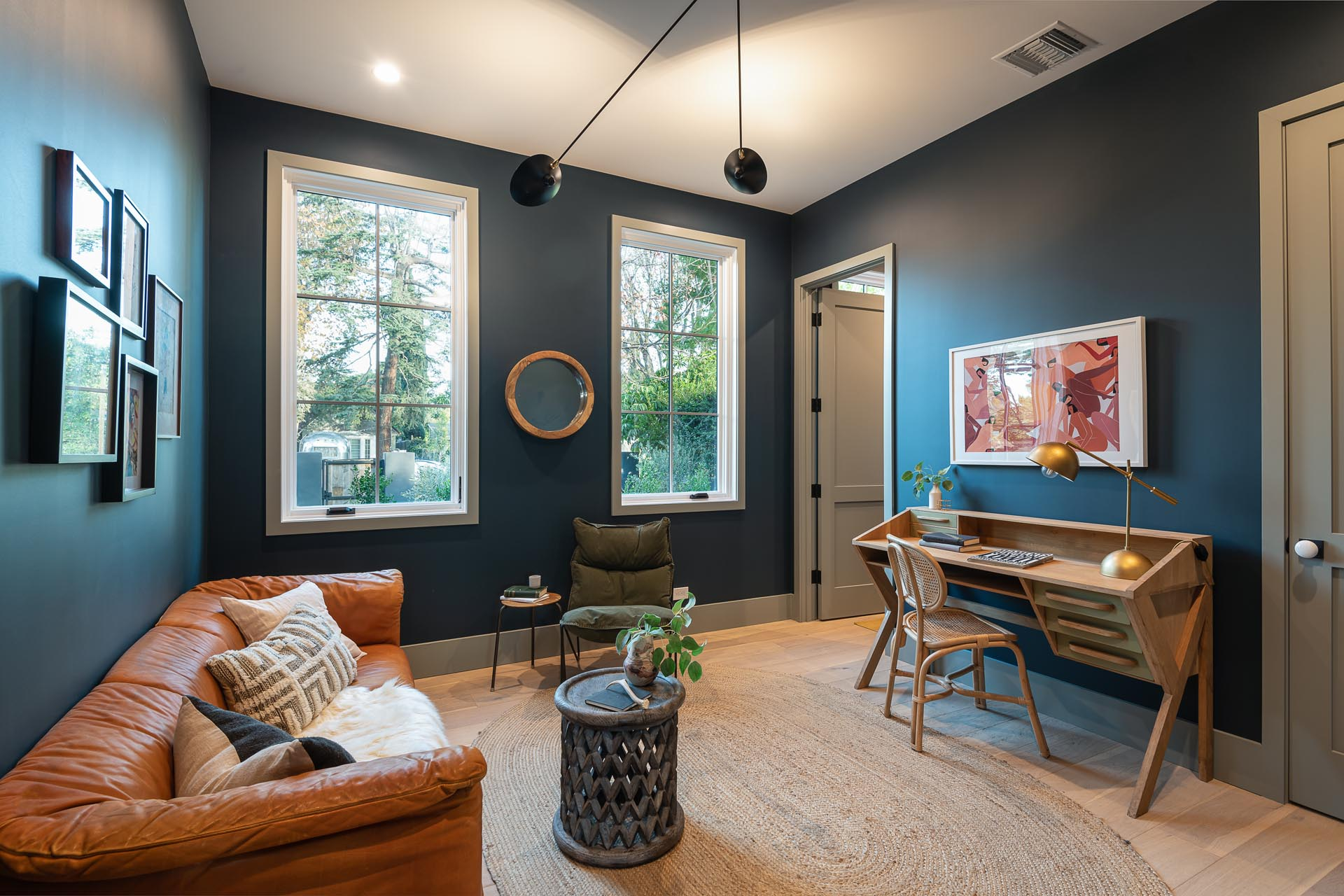 A modern home office with white framed windows, dark walls, a leather sofa, and a wood desk.