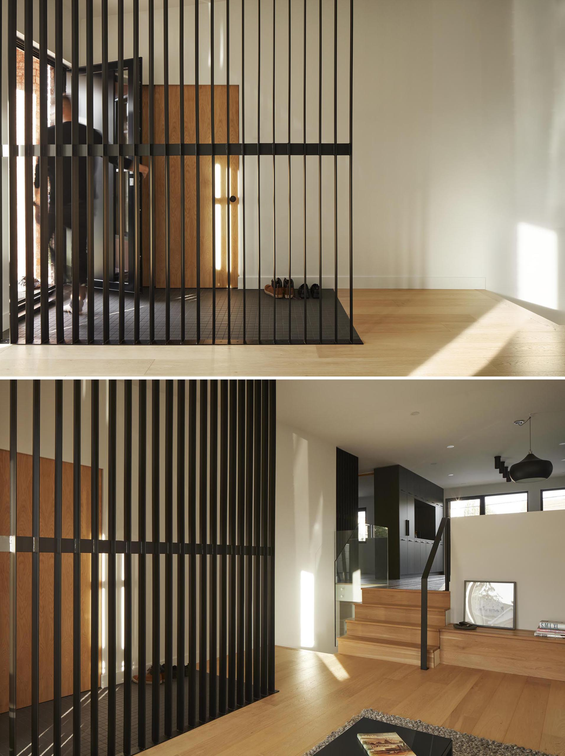 This modern room divider, which also complements the dark tiled floor, allows the light from the living room to travel through to the entryway.