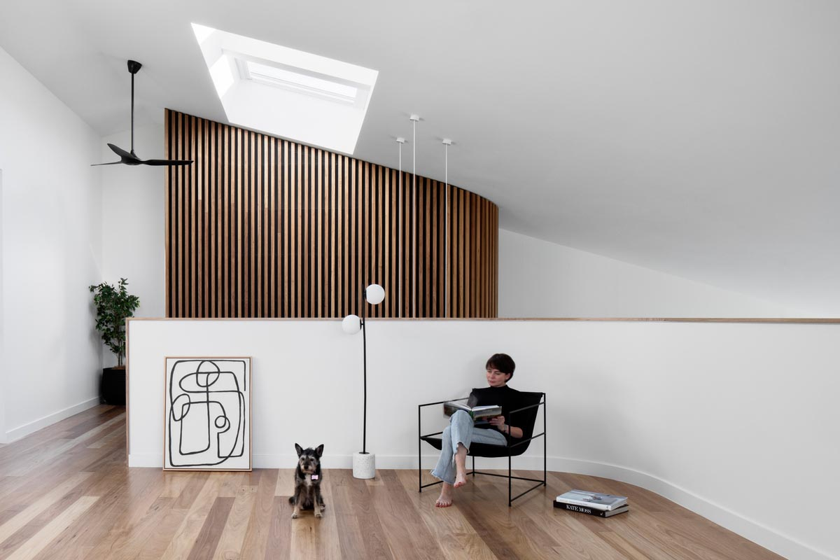The wood slat wall is visible from an open area with a skylight, and a balcony that overlooks the lower level.