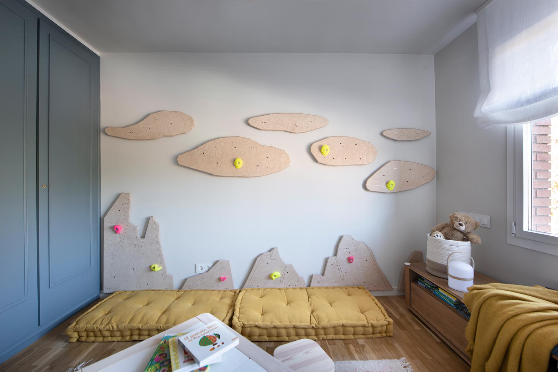 In this modern kid's bedroom, there's uniquely shaped wood cut-outs on the wall that have been designed to attach rock climbing mounts, turning the one empty wall into a climbing wall.